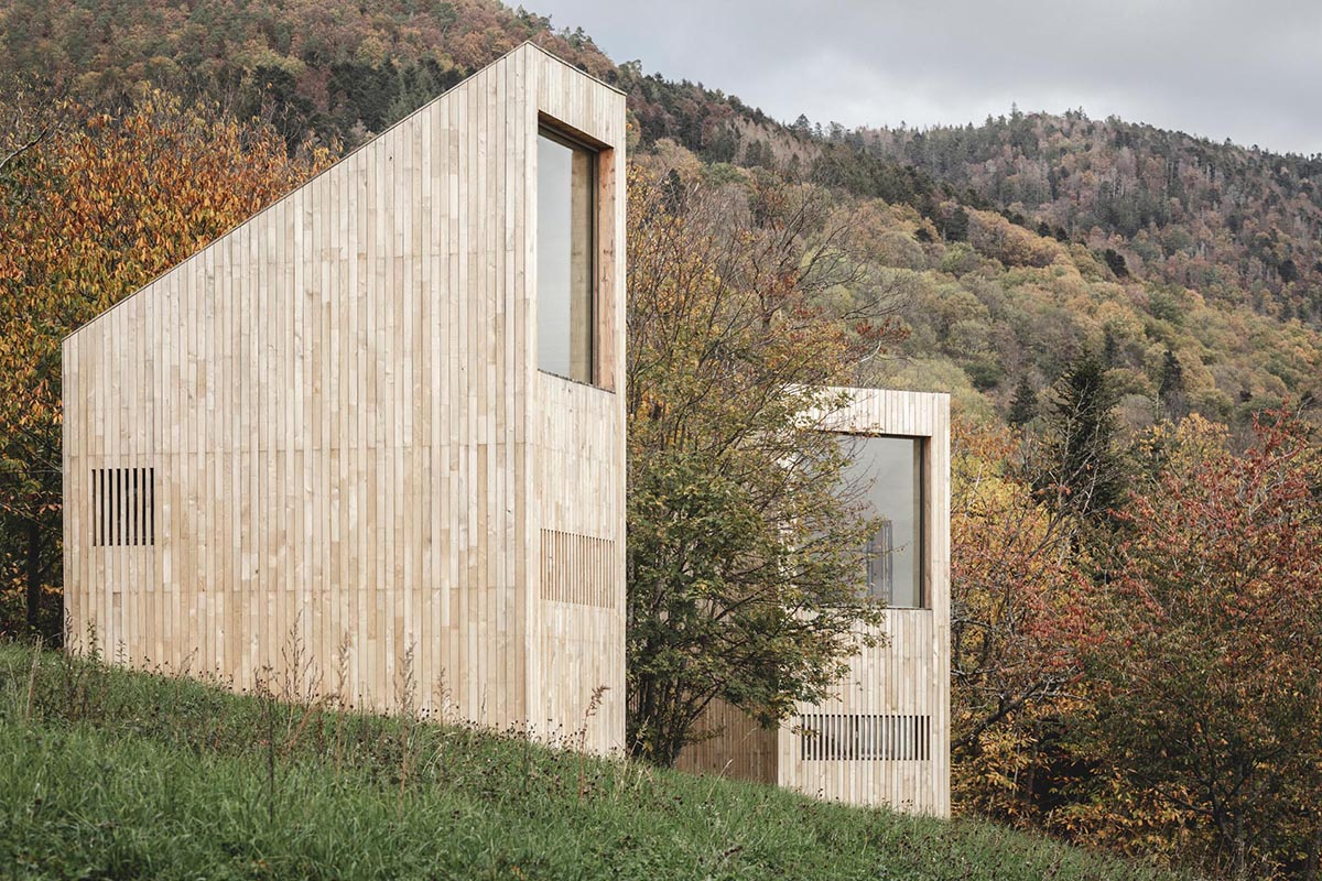 Modern cabins with a vertical design, light wood exterior, and large windows.