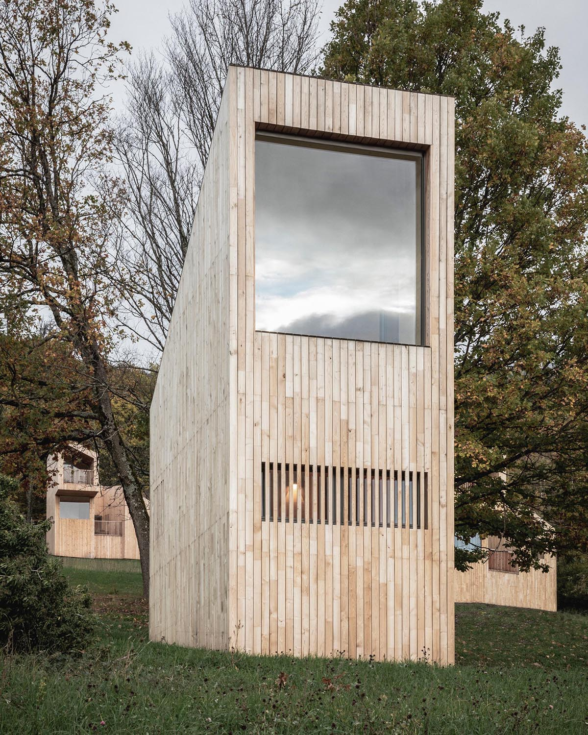 A collection of small wood cabins designed as part of a hotel in France.