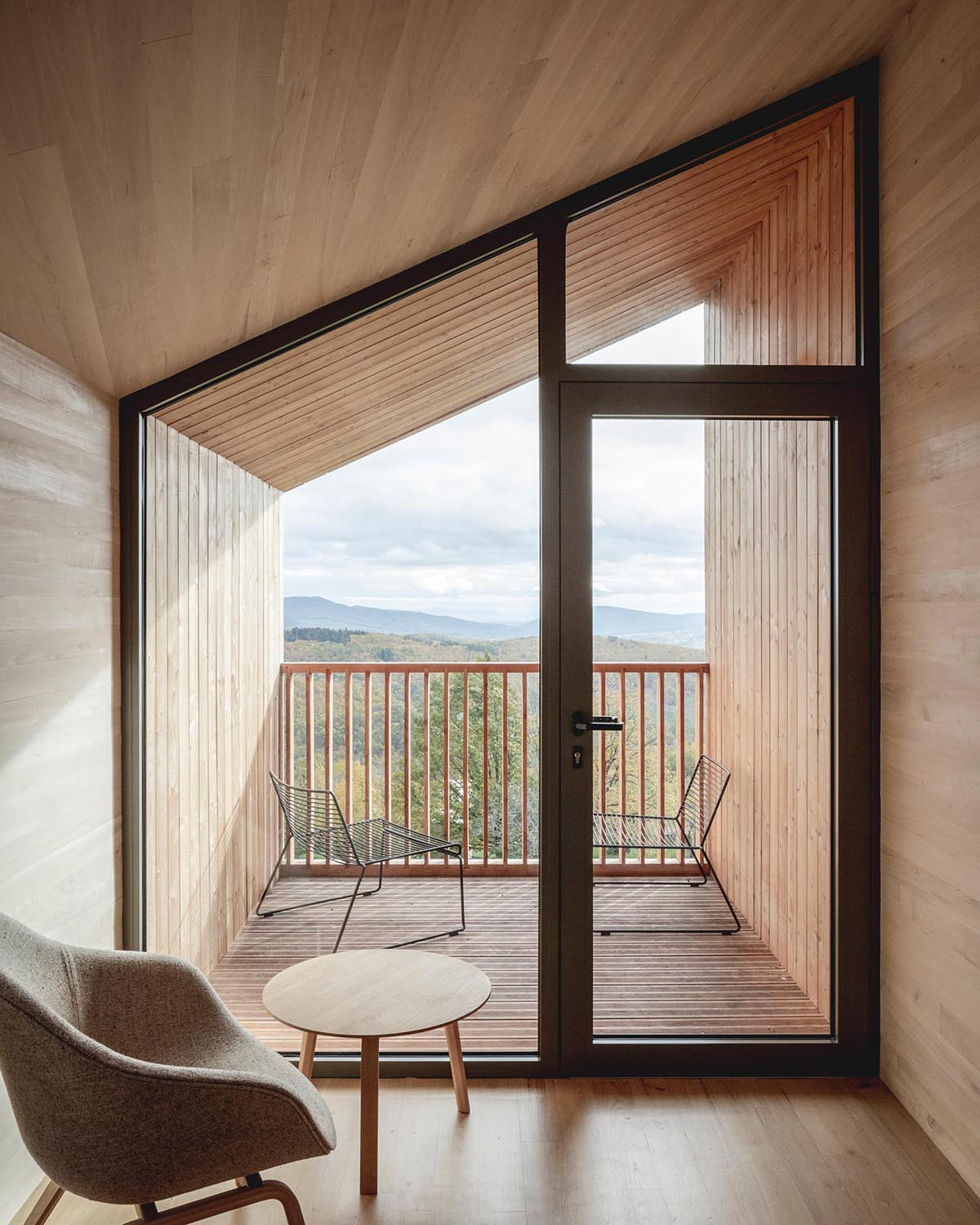 A modern cabin with a wall of glass that opens to a small covered balcony.