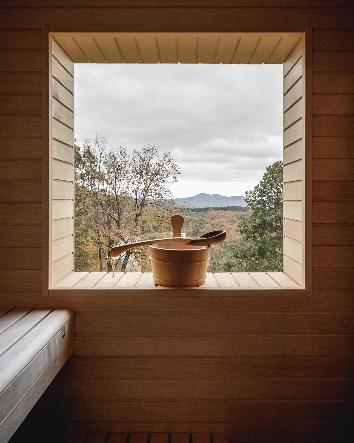 A modern sauna with built-in furniture and light wood interior.
