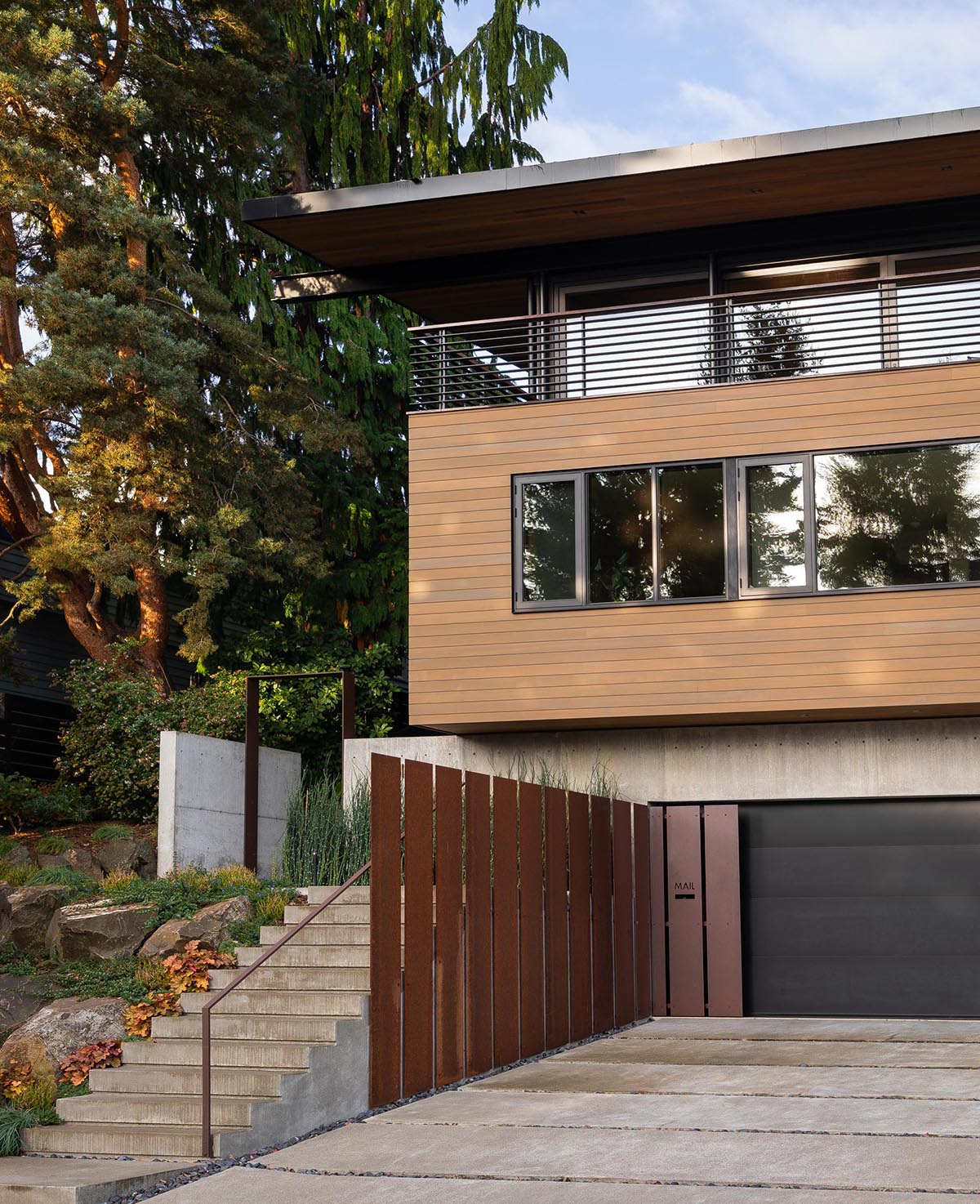 The facade of this modern house features a concrete, a black garage door, steel accents, wood siding, and steps that lead to the front door.