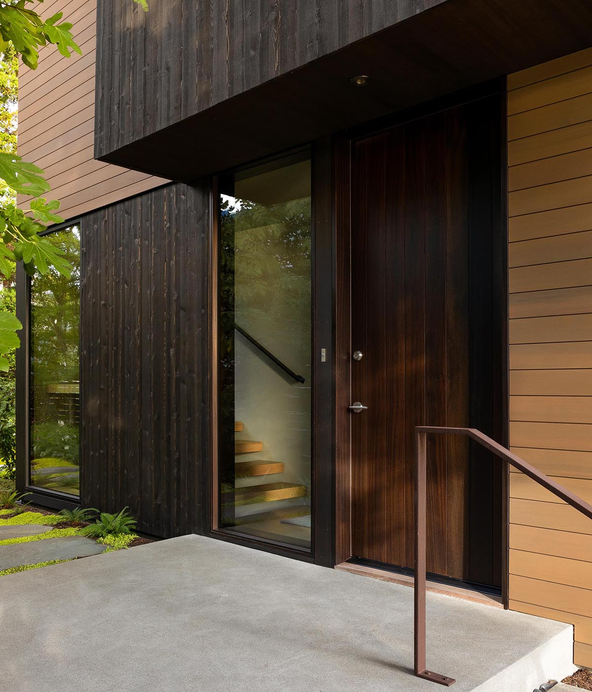 Black wood siding and a dark front door greet visitors to this modern home.