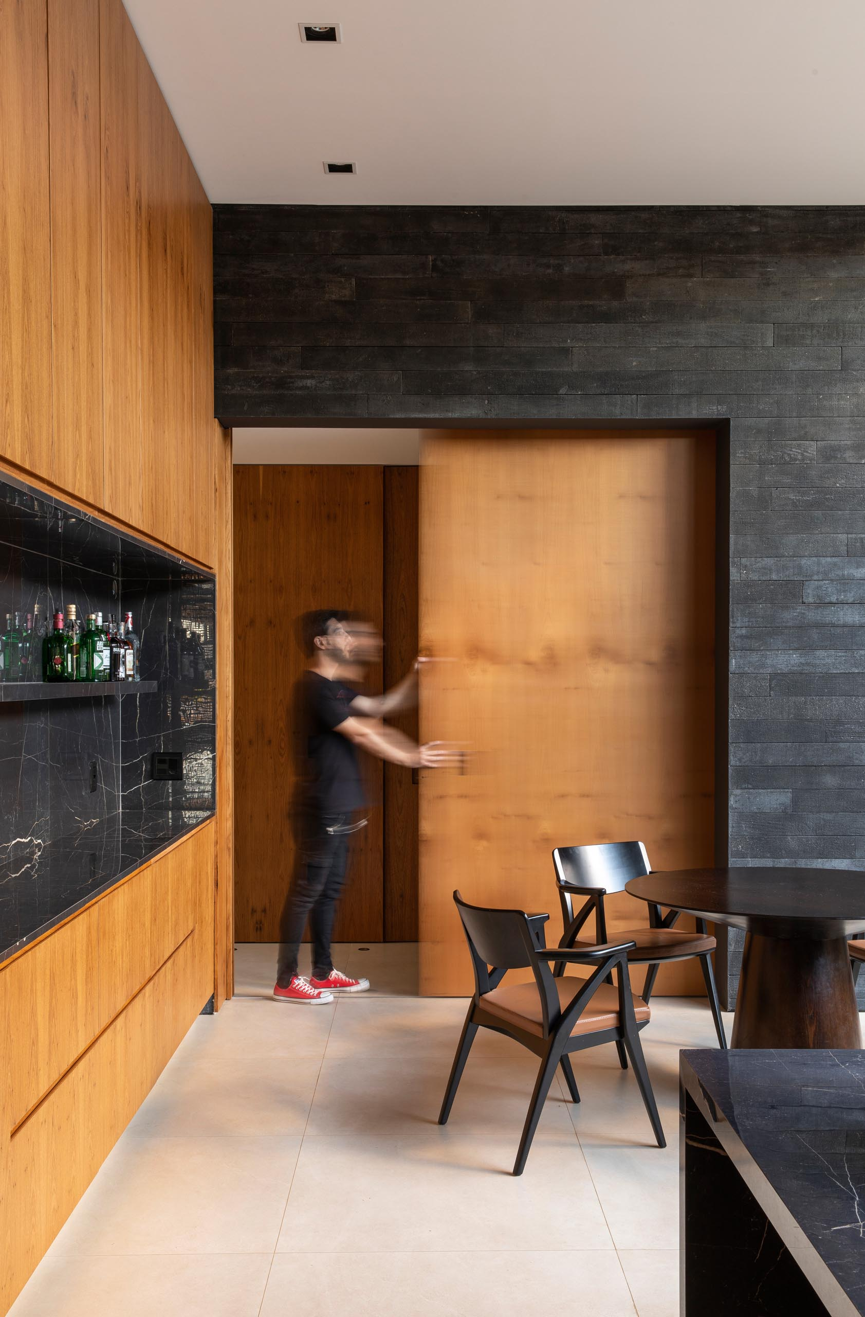 A modern black and wood kitchen with a sliding pocket door.