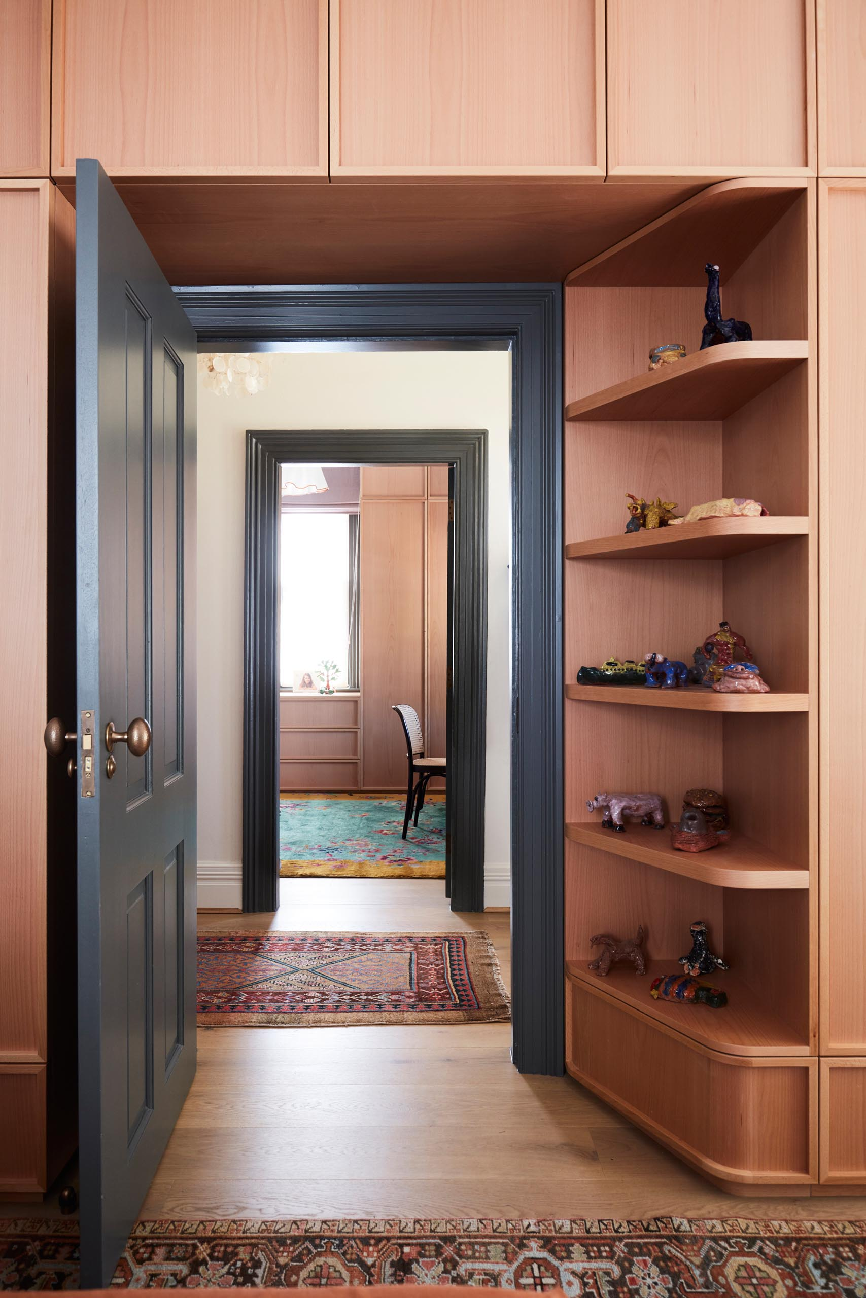 Custom-designed wood storage cabinets with open shelving that wrap around the door.