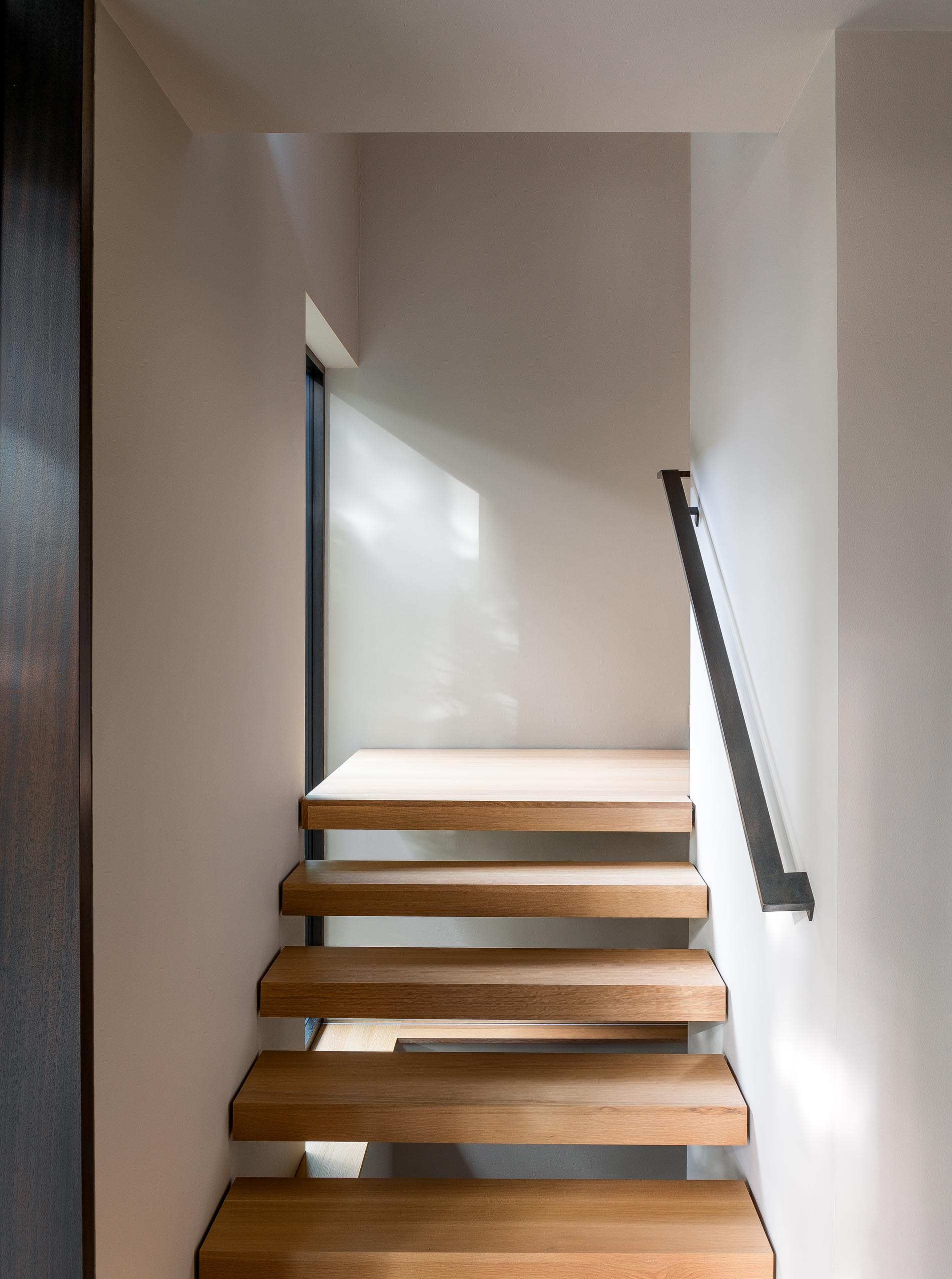 Wood stairs connect the upper social areas of this modern home with the bedrooms and bathrooms that are located on the lower level.