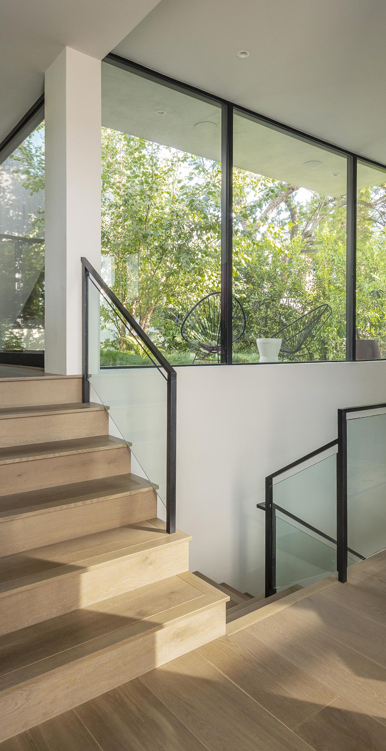 Connecting the various levels of this modern house are wood stairs that have a glass and metal railing.