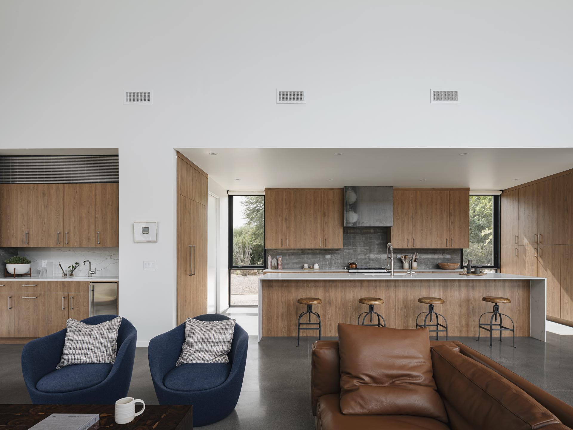 The wood cabinetry in the kitchen has been installed right up against the board-formed concrete wall, while a long kitchen island creates plenty of counter space.