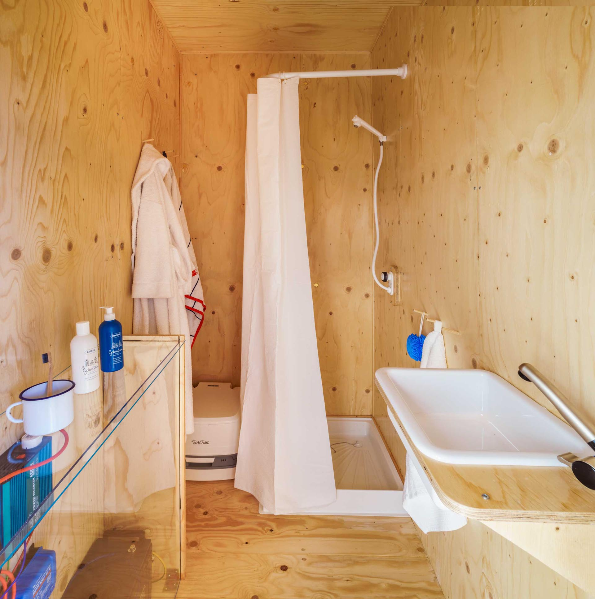 A tiny home made from a shipping container has a plywood lined bathroom with a shower.