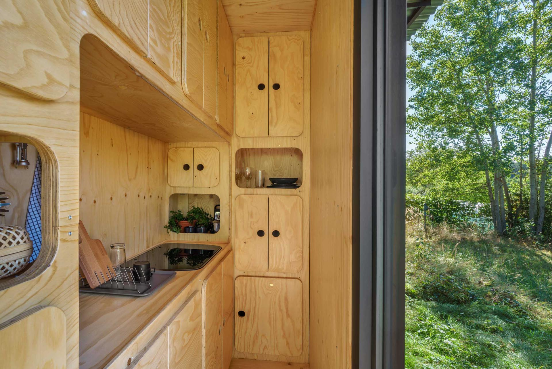 A plywood kitchen inside a tiny home made from a small shipping container.