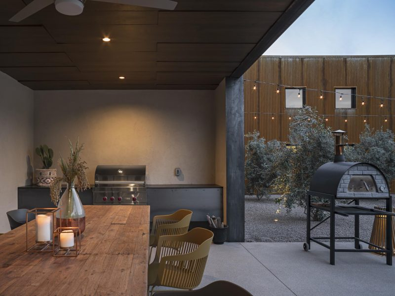 A modern outdoor kitchen with a covered dining area.
