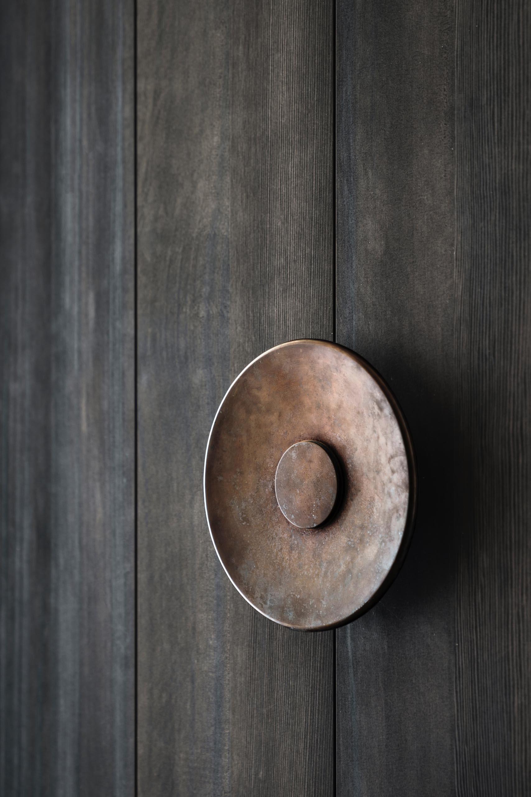An oversized metal door handle for a large floor-to-ceiling pivoting wood front door.