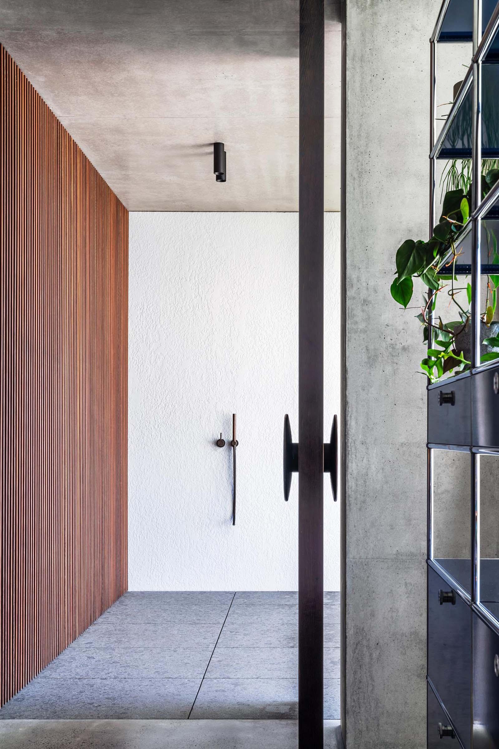 An oversized pivoting wood front door.
