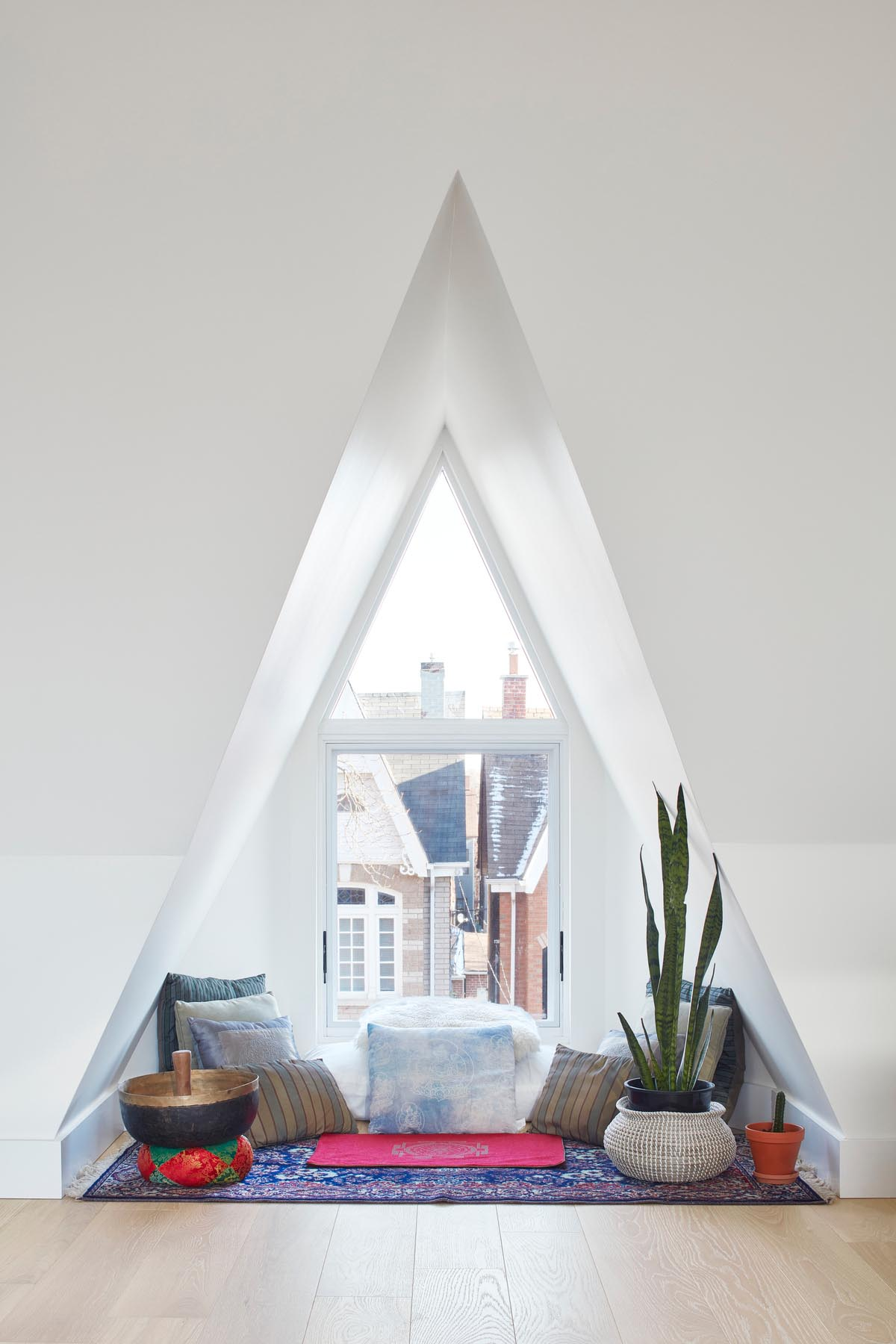 A triangular window nook that been furnished with a rug, plenty of pillows, plants, and a meditation bowl.