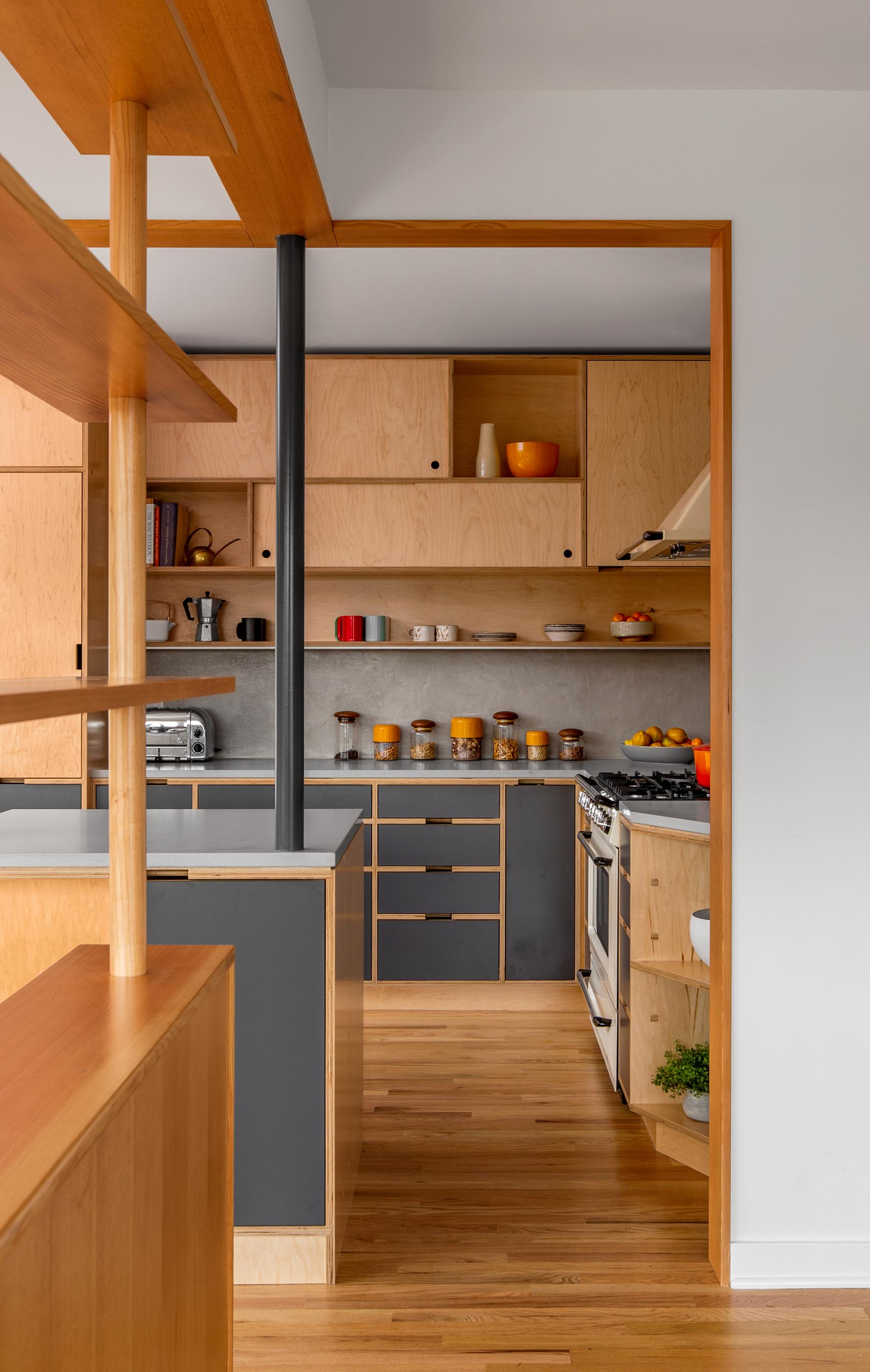 A modern custom-designed kitchen with wood and gray cabinets.