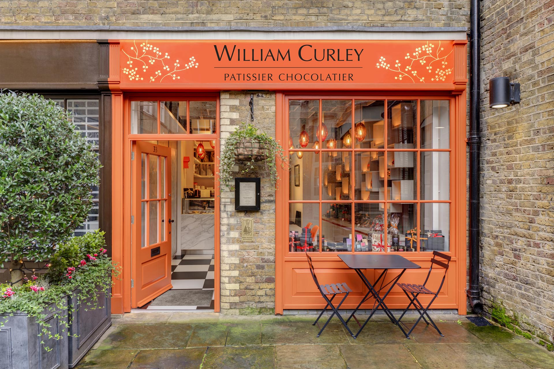 A modern chocolatier with a vivid orange facade that draws inspiration from the lid of the boxes the chocolates are packaged in.