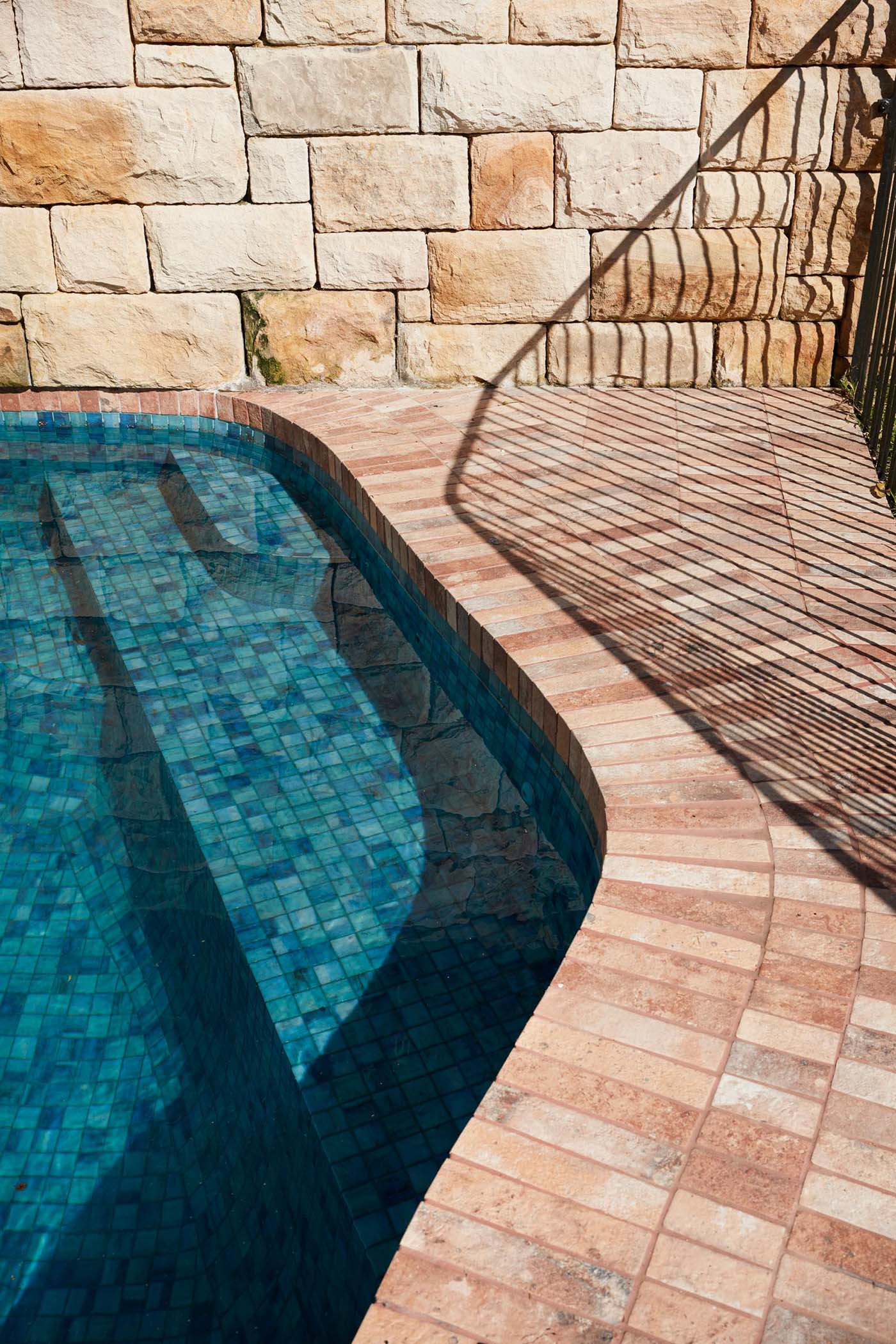 A contemporary pool with brick patio and sandstone wall.
