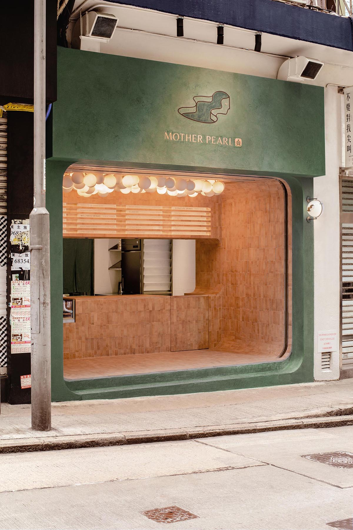 A modern bubble tea house with an olive green facade and a earth colored tiled interior.