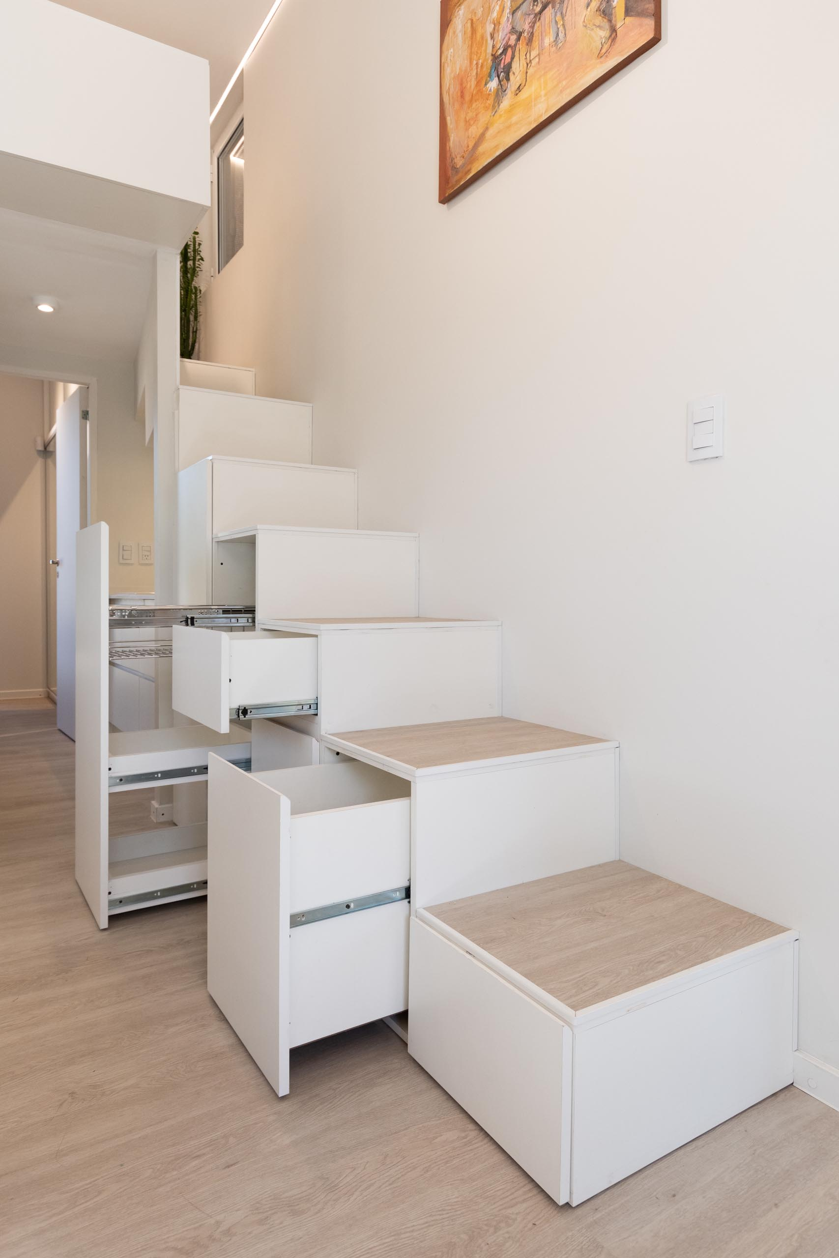 A modern home with a staircase that includes storage and leads to a mezzanine level.
