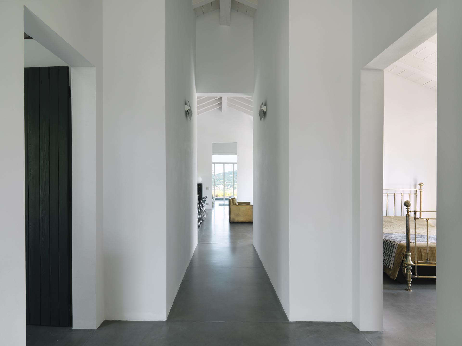 A modern farmhouse hallway with white lime tempera walls and concrete floors.