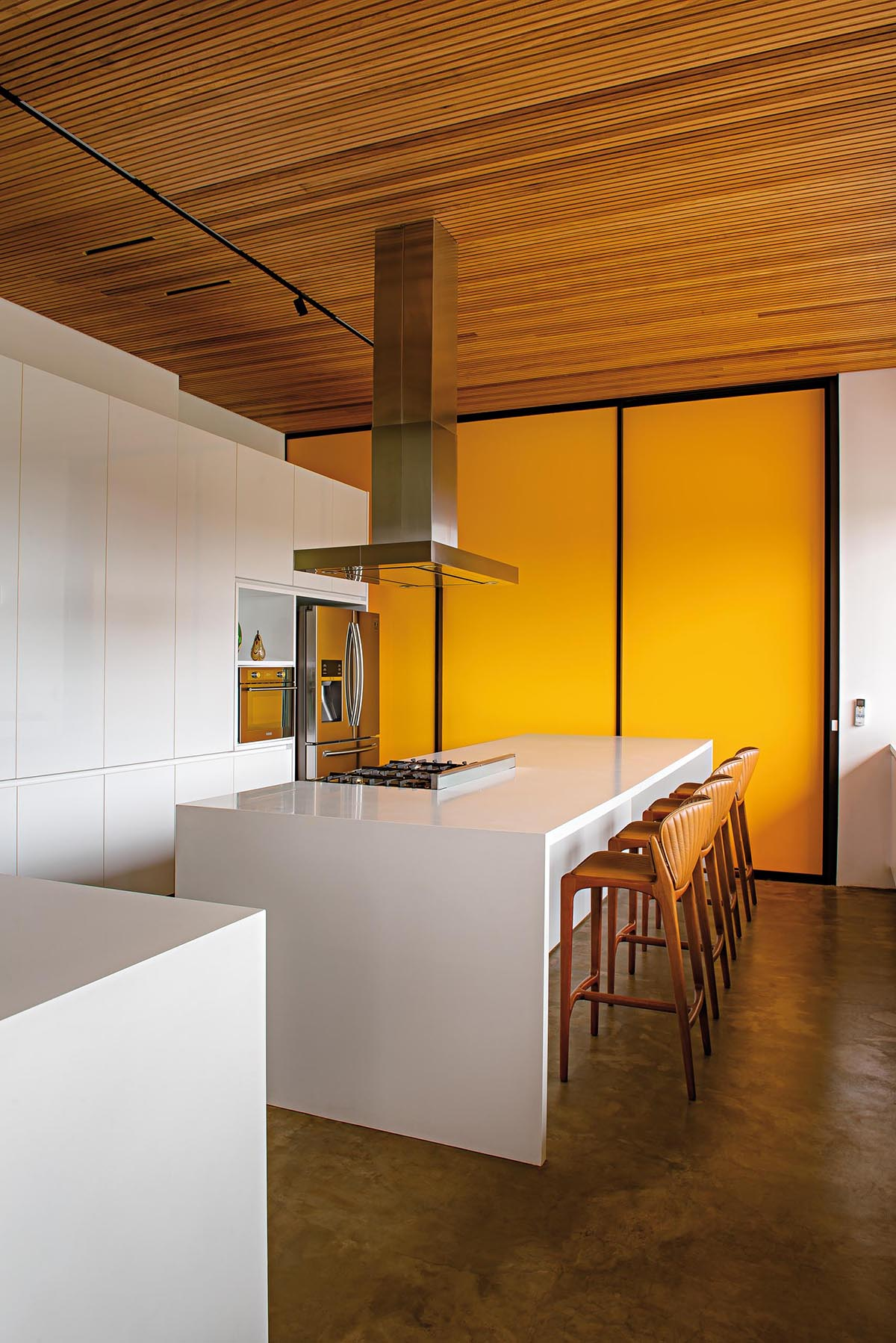 This modern kitchen has minimalist hardware-free white cabinets and island. A bright yellow accent wall creates a bold and colorful statement.