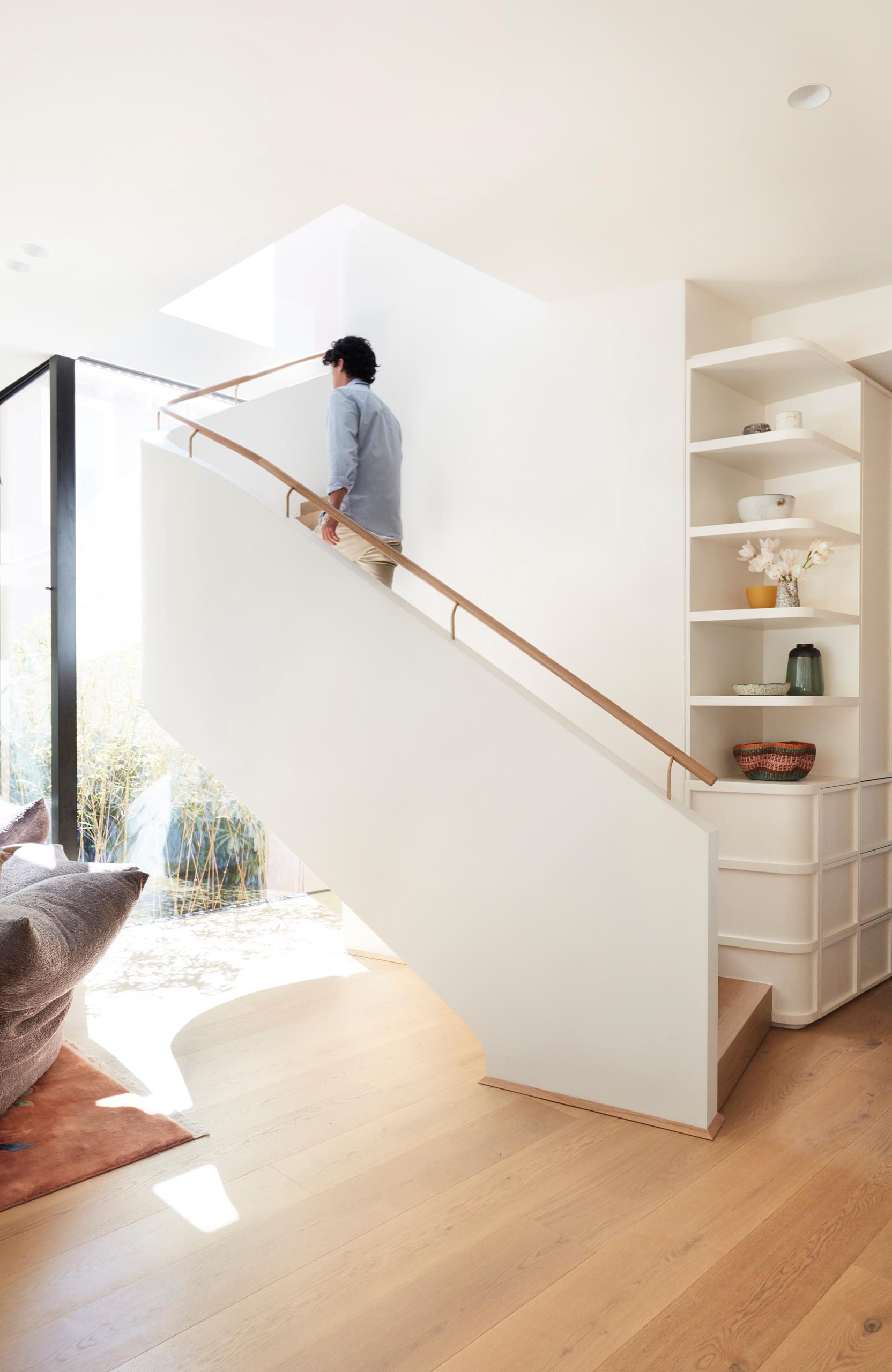 White stairs connect the living spaces with the bedrooms and bathrooms upstairs.