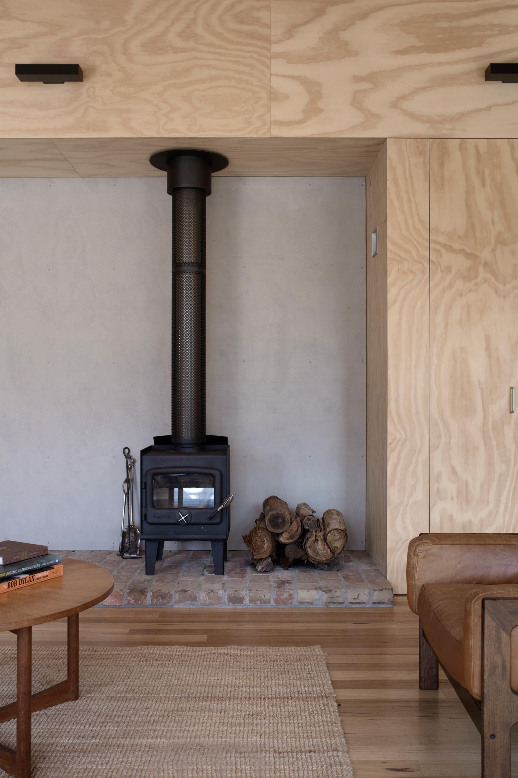 Salvaged bricks were reused in the hearth of this fireplace, which has a matte black finish to match the ceiling fan.