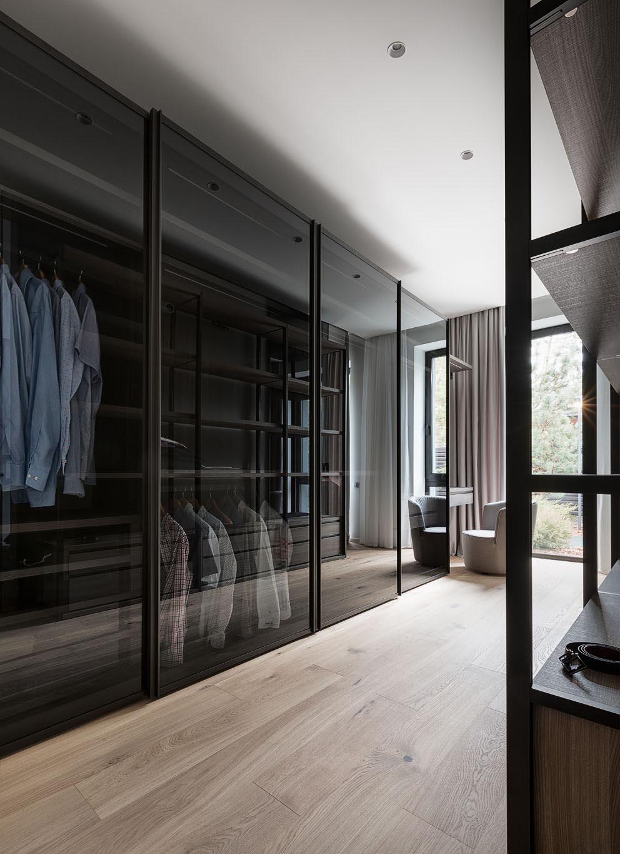 A modern walk-through closet includes black glass doors.
