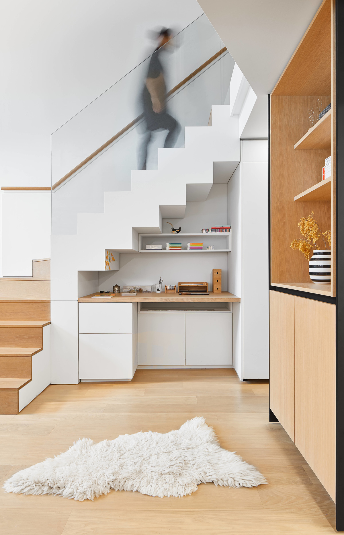 A modern desk has been built underneath the stairs of this loft apartment.