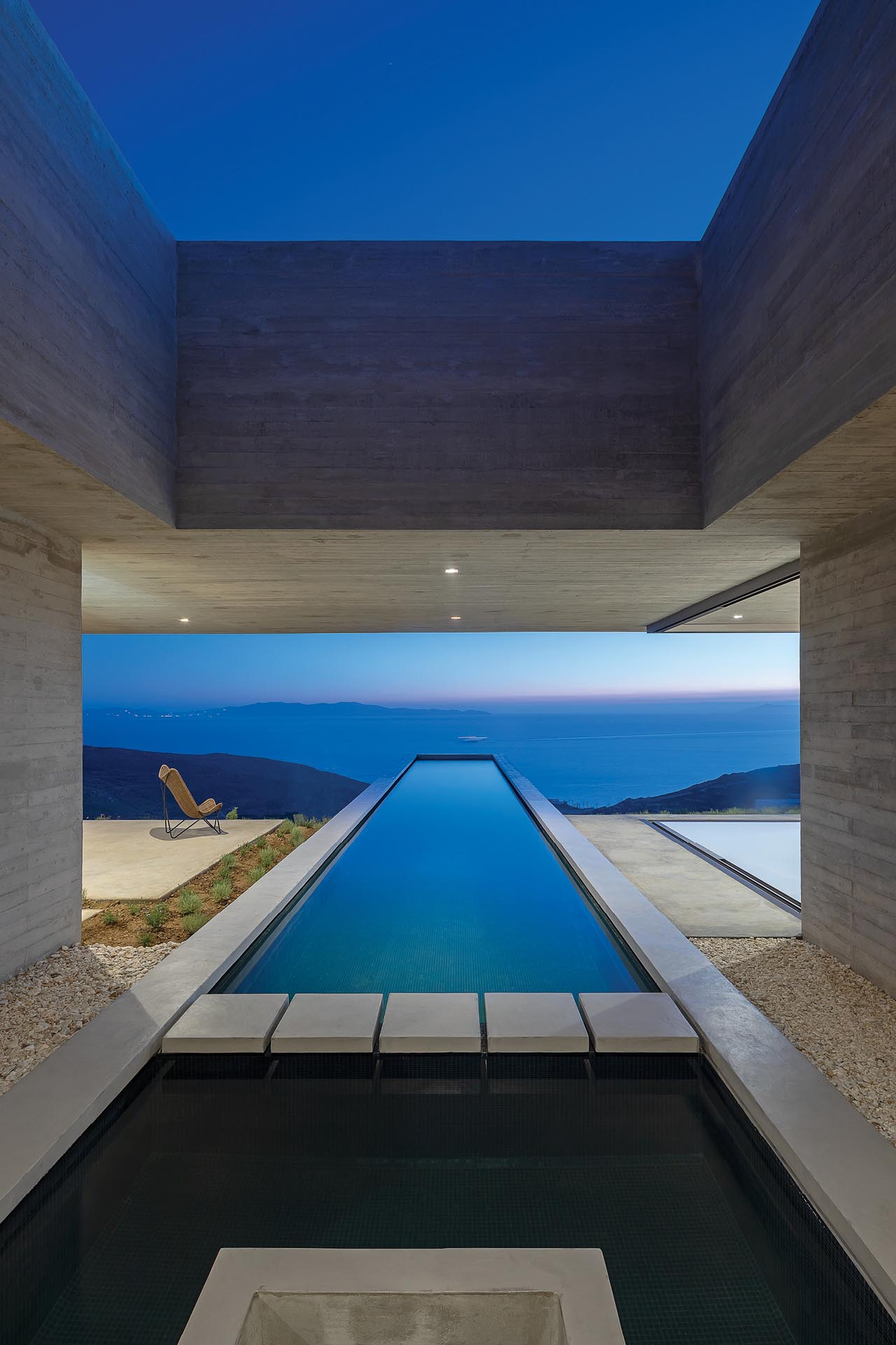 A modern concrete house with a linear swimming pool.