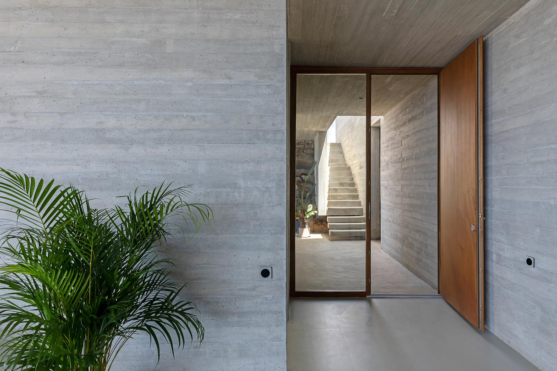 A modern concrete home with a large wood front door.