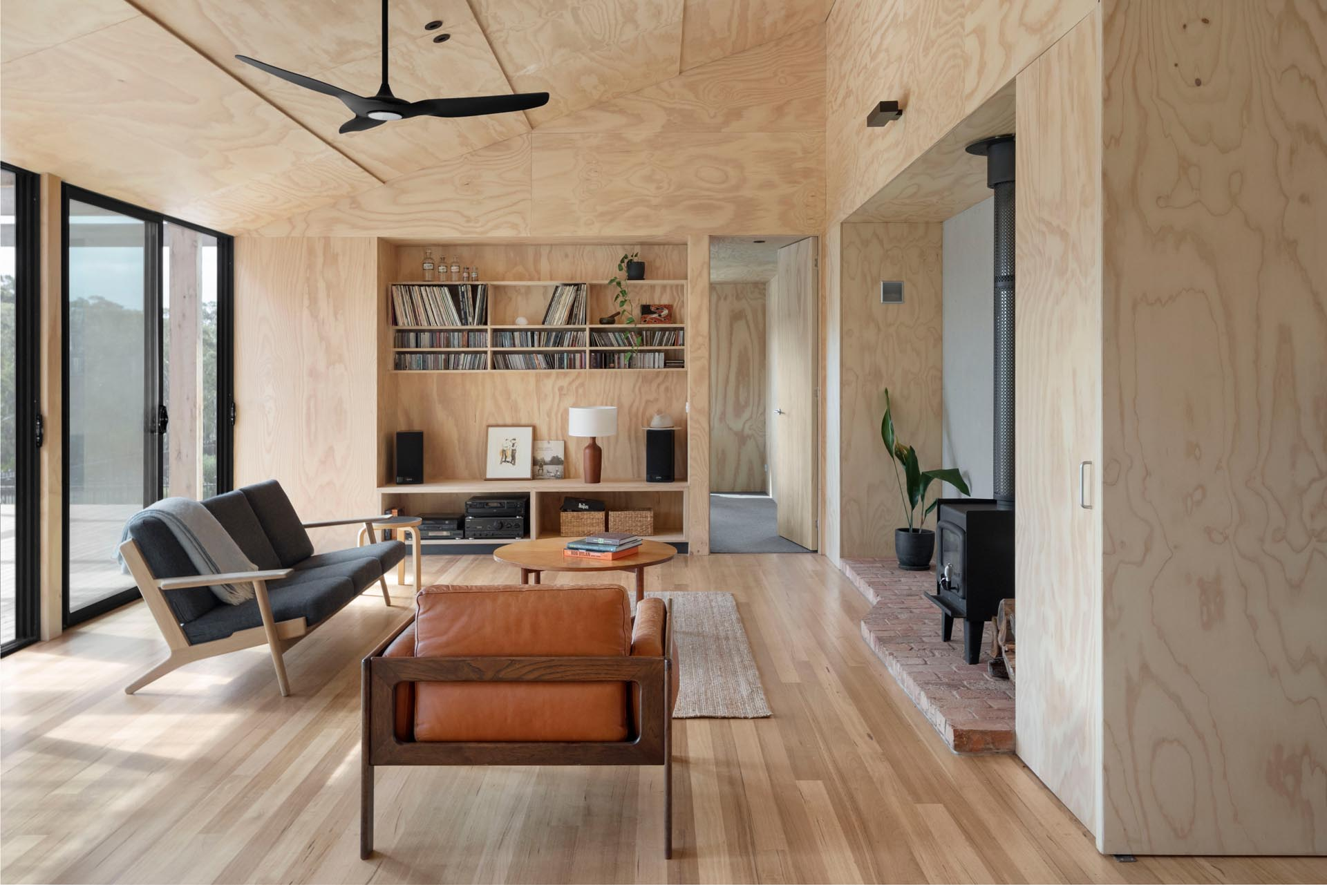 The interior of this home has been lined with plywood sheets, designed to age gracefully instead of repainting in the future.
