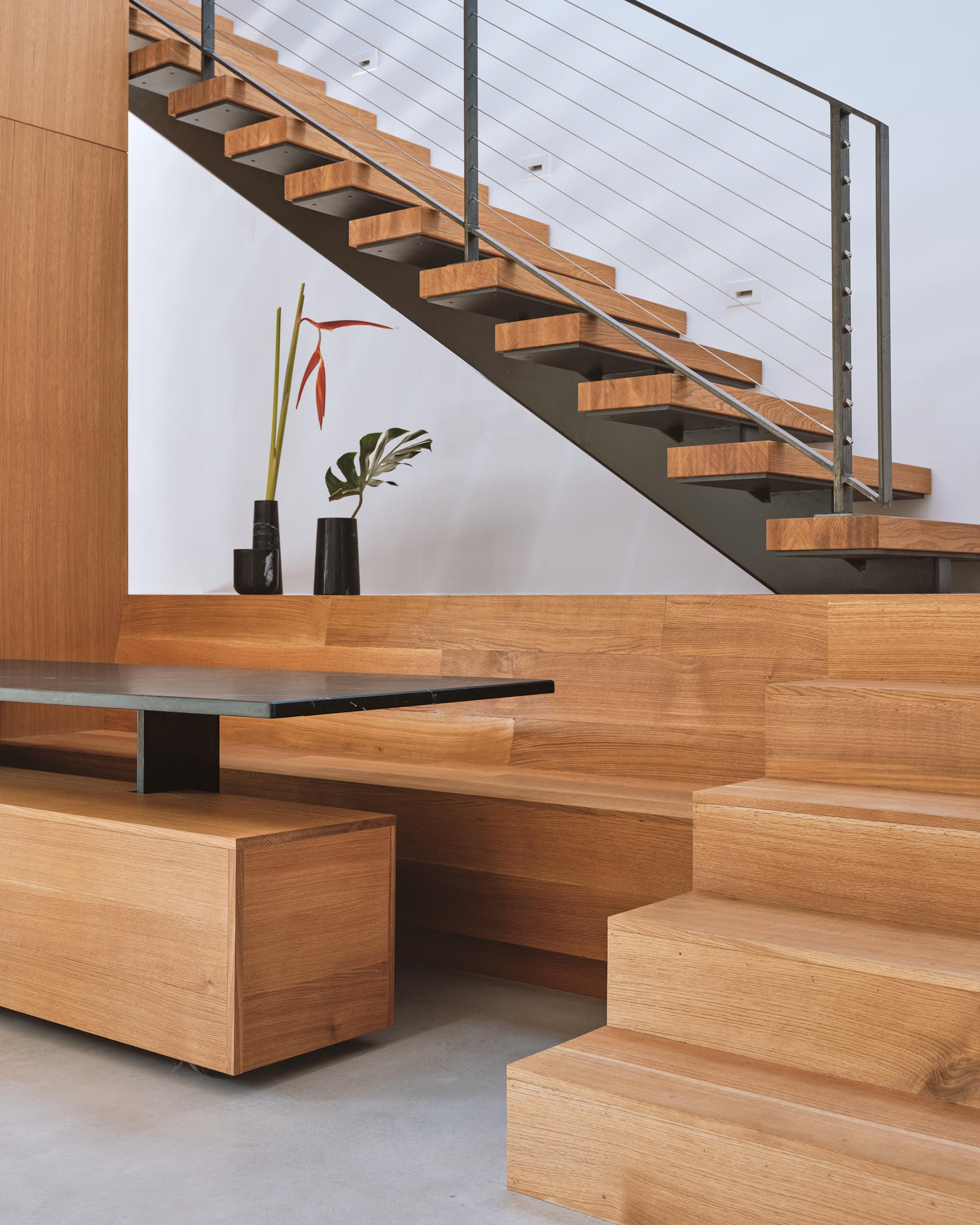 A modern built in dining area with benches and a dark table top.
