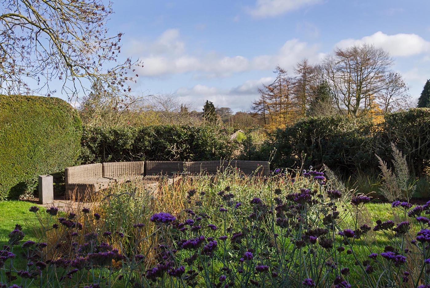 A large outdoor sofa tucked away into a garden.