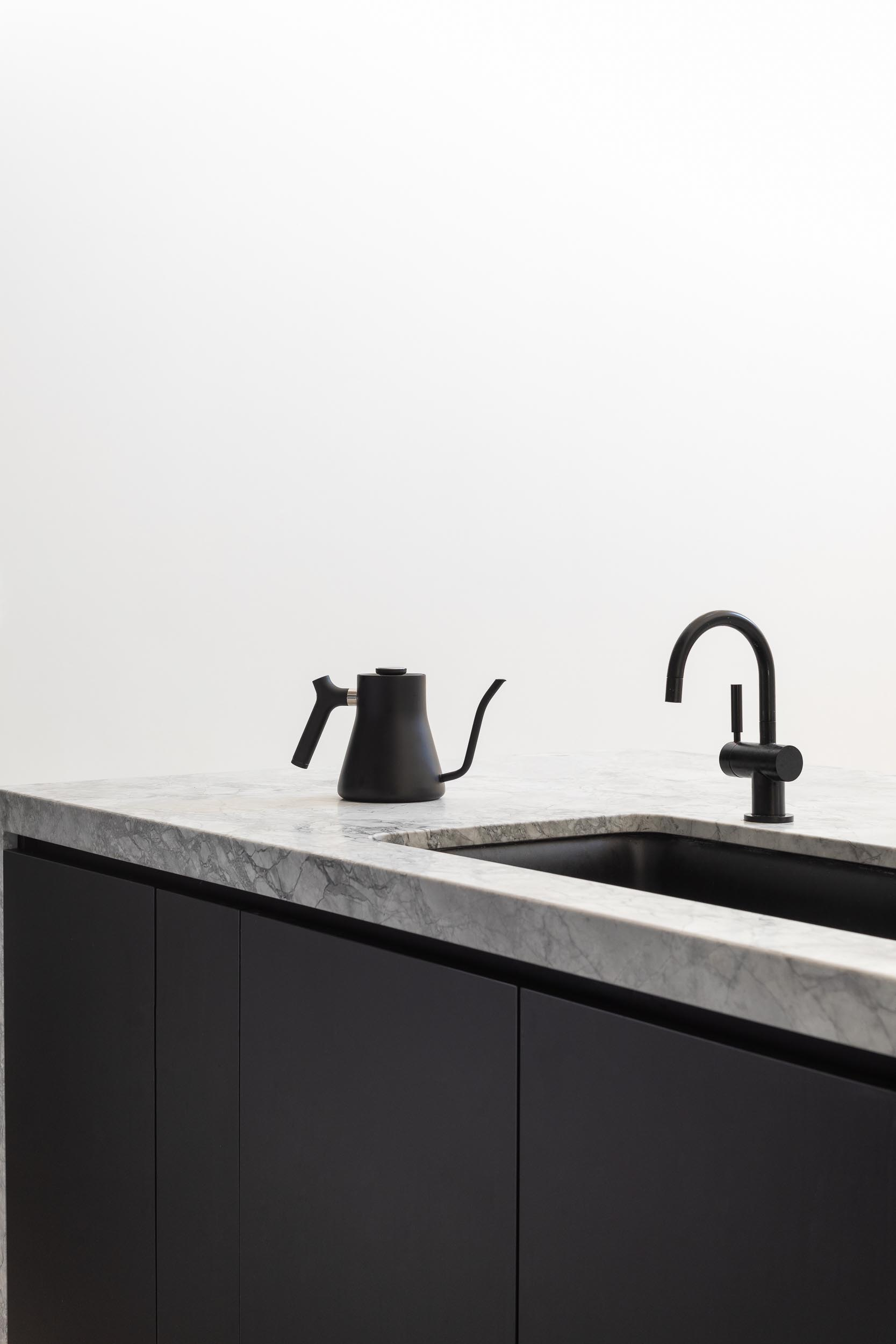 A modern kitchen island with matte black cabinets, and a matching matte black sink and faucet.