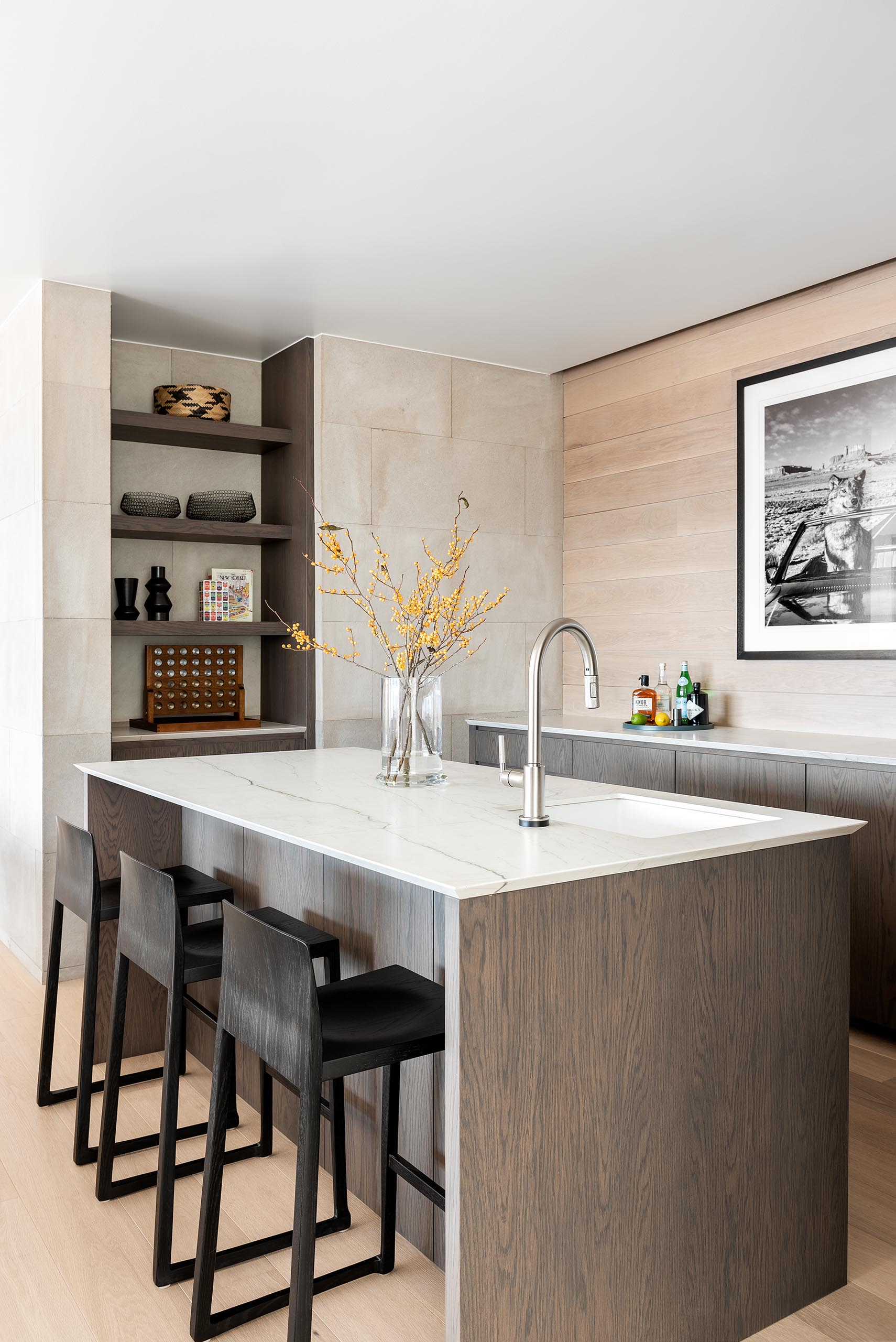 A modern bar with an island, wood cabinets, open shelving, and light colored countertops.