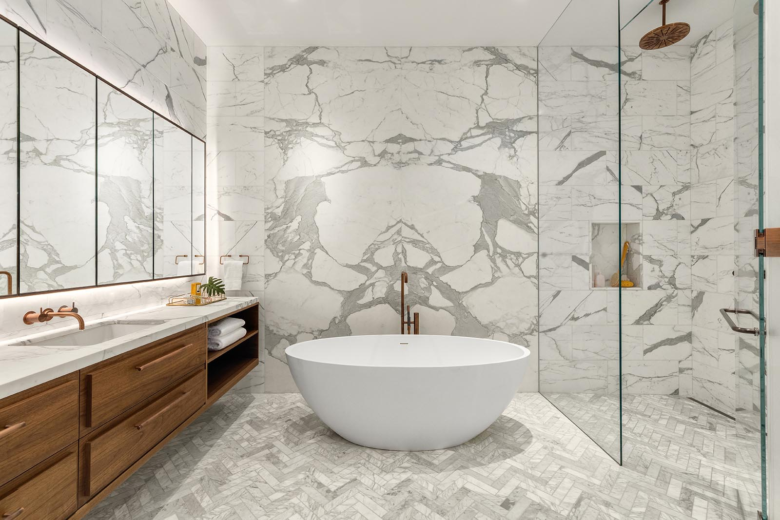 This modern master bathroom includes gray and white book-matched marble slabs on the walls, a floating wood vanity, a freestanding Badeloft bathtub, and a glass enclosed shower.