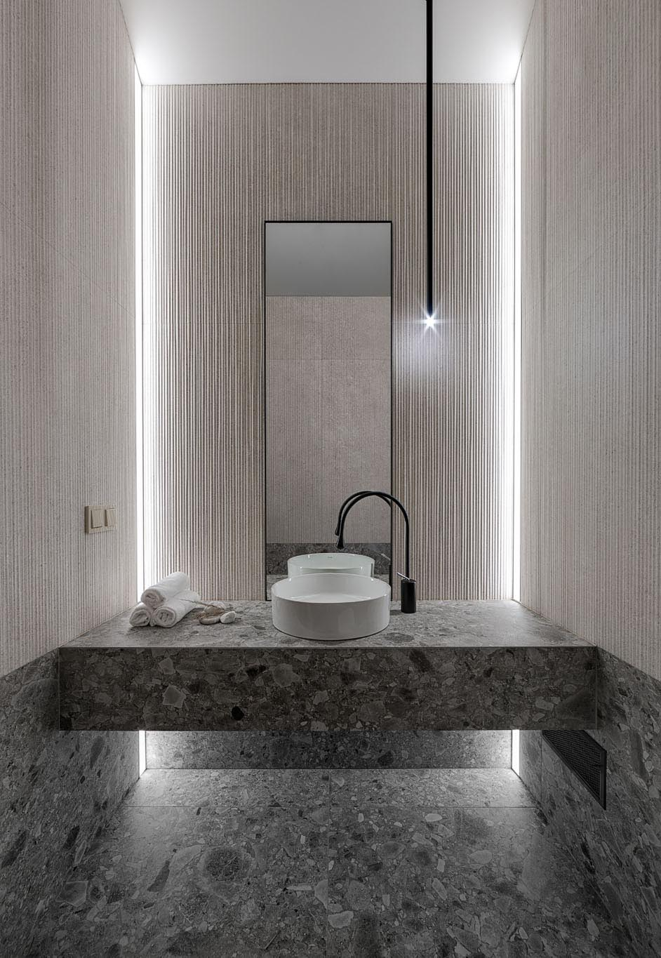 In this modern bathroom, there's simple textured walls, a minimalist light fixture, and a stone vanity and matching flooring.