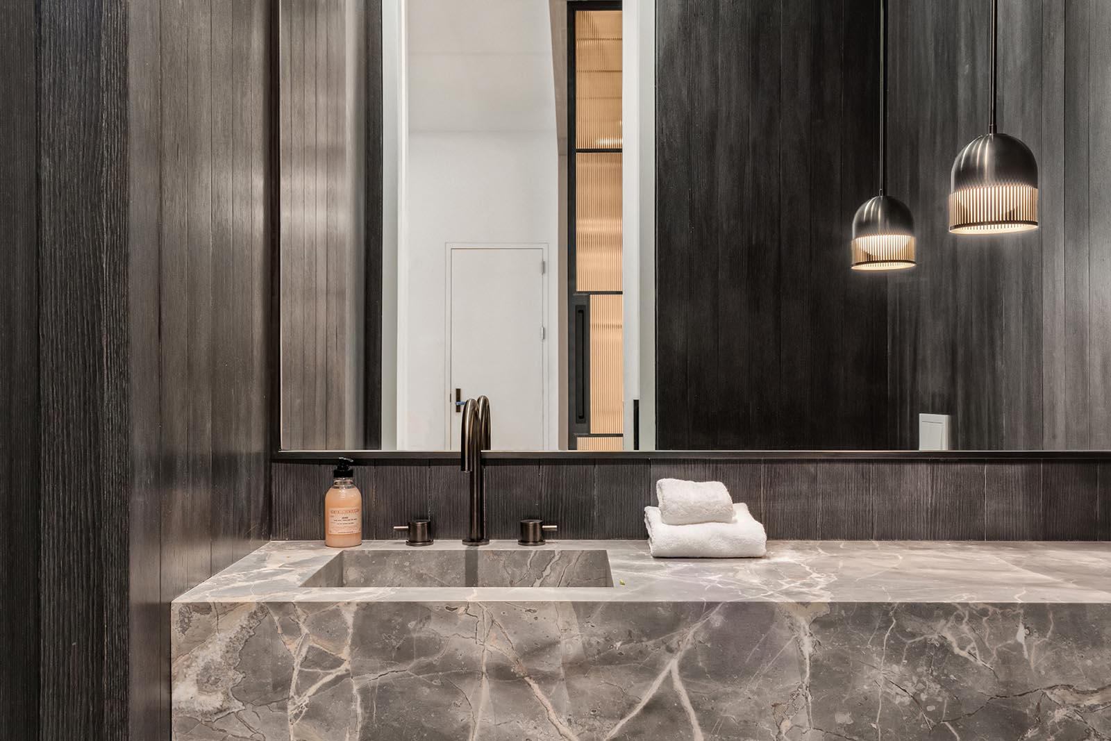 In this modern bathroom, dark wood walls have been used to create a dramatic appearance.