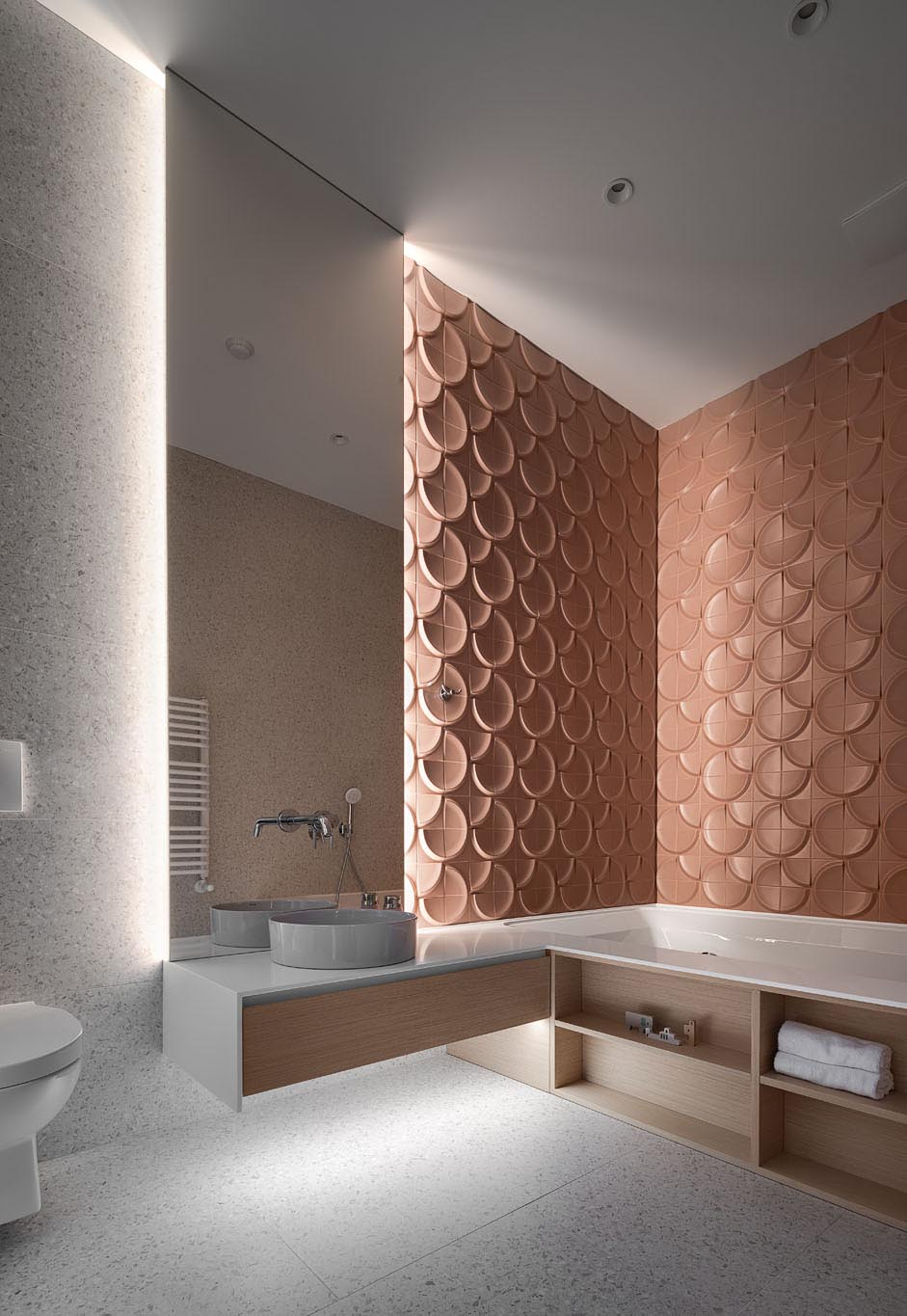 In this modern bathroom, 3-dimensional wall tiles create a unique textured look that's accentuated by the lighting coming from the backlit mirror.