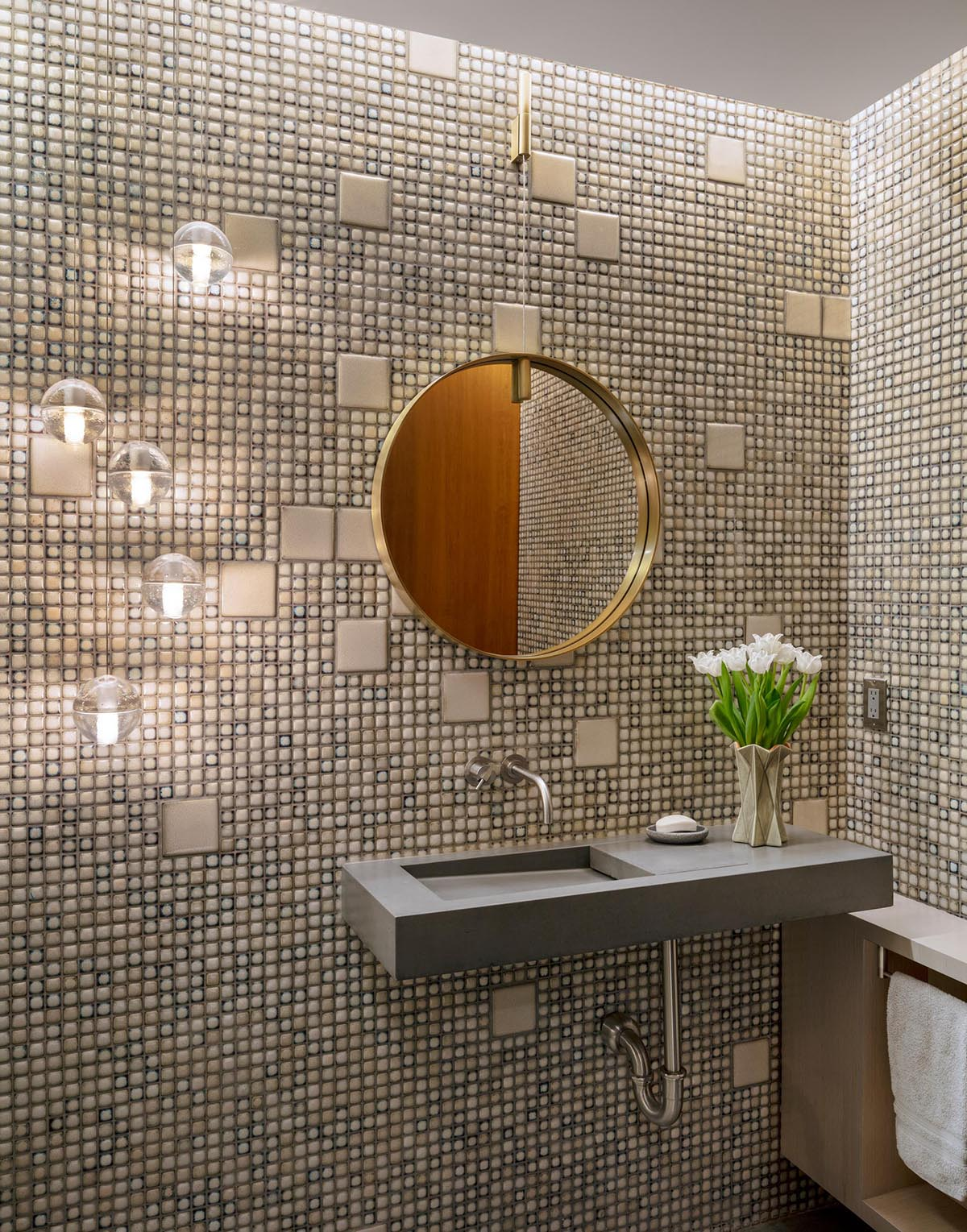In this powder room, there's a combination of small and large tiles covering the walls, while a round mirror hangs above a concrete vanity.
