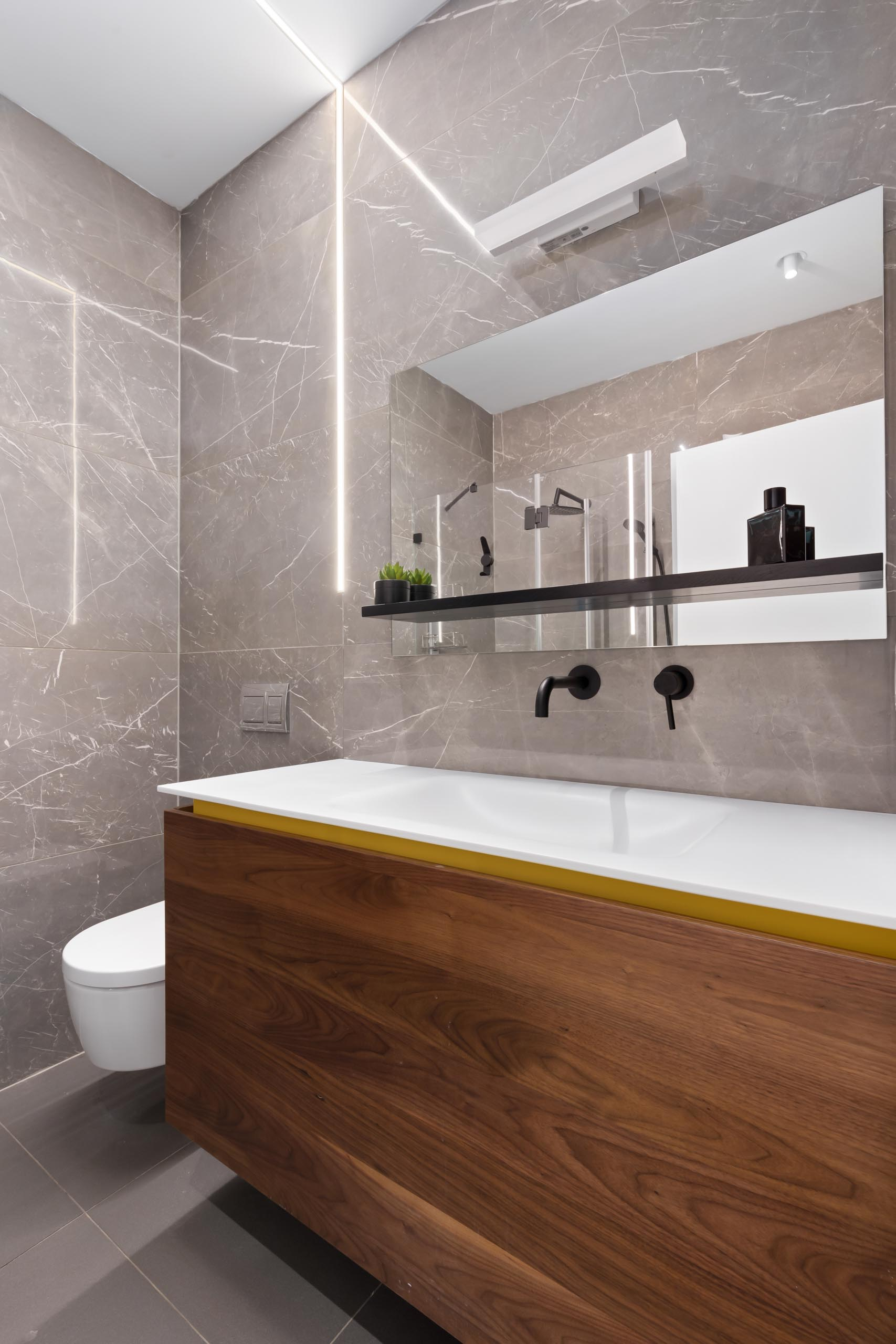 A modern bathroom with a wood vanity that includes a hint of yellow.