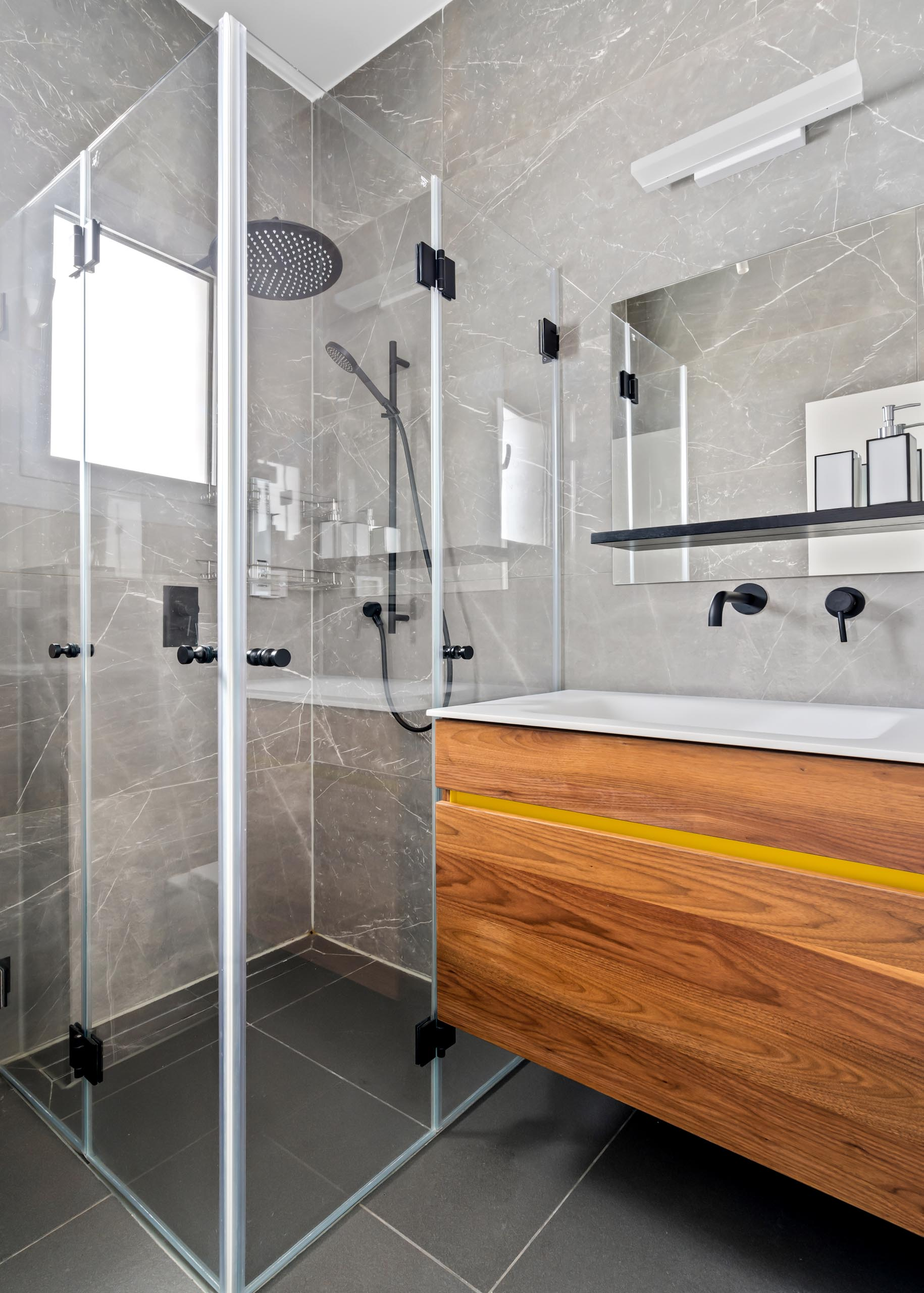 In this guest bathroom, there's a wood vanity with a simple yellow strip for a unique touch.