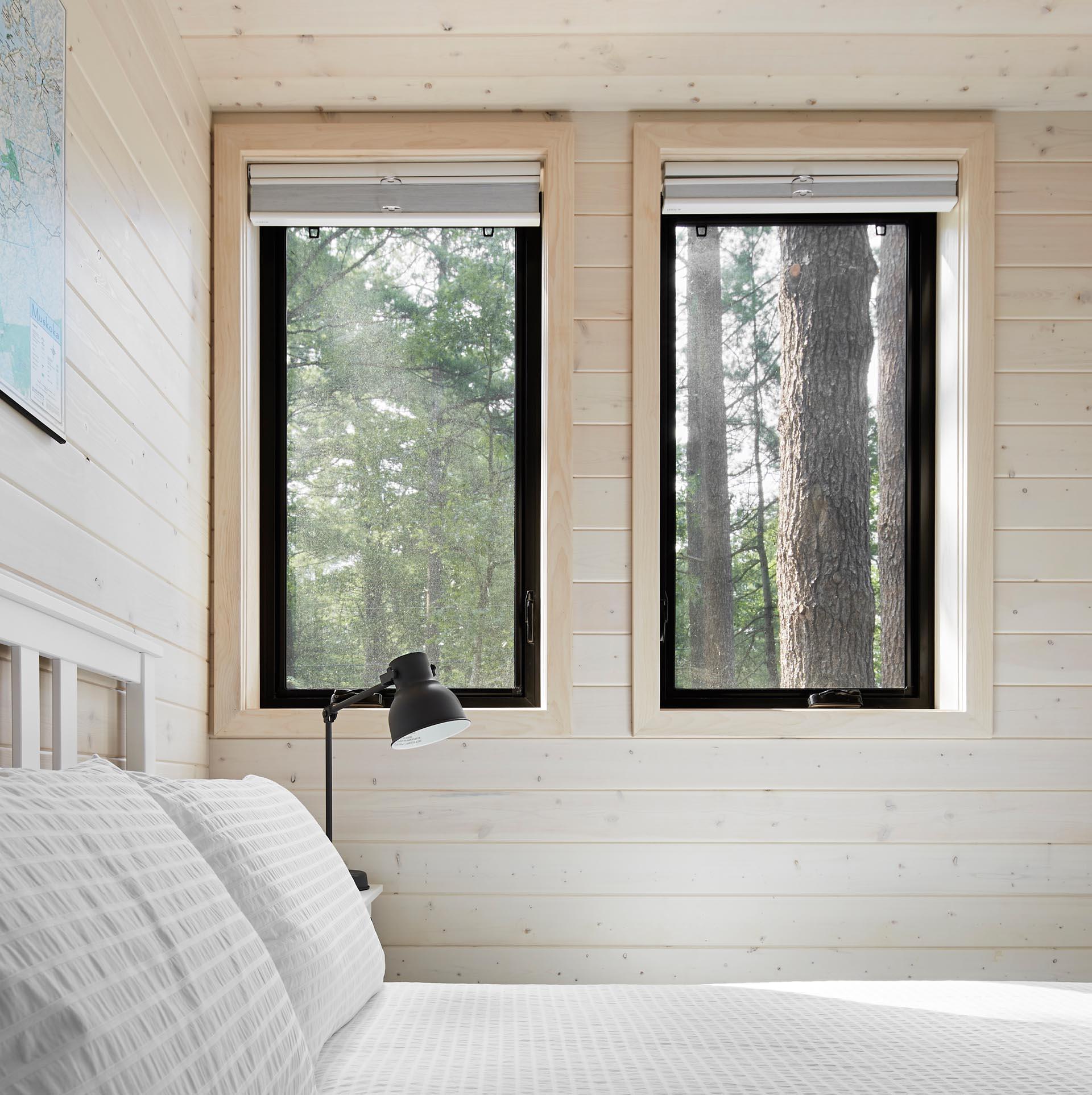 A modern cottage bedroom with black window frames.