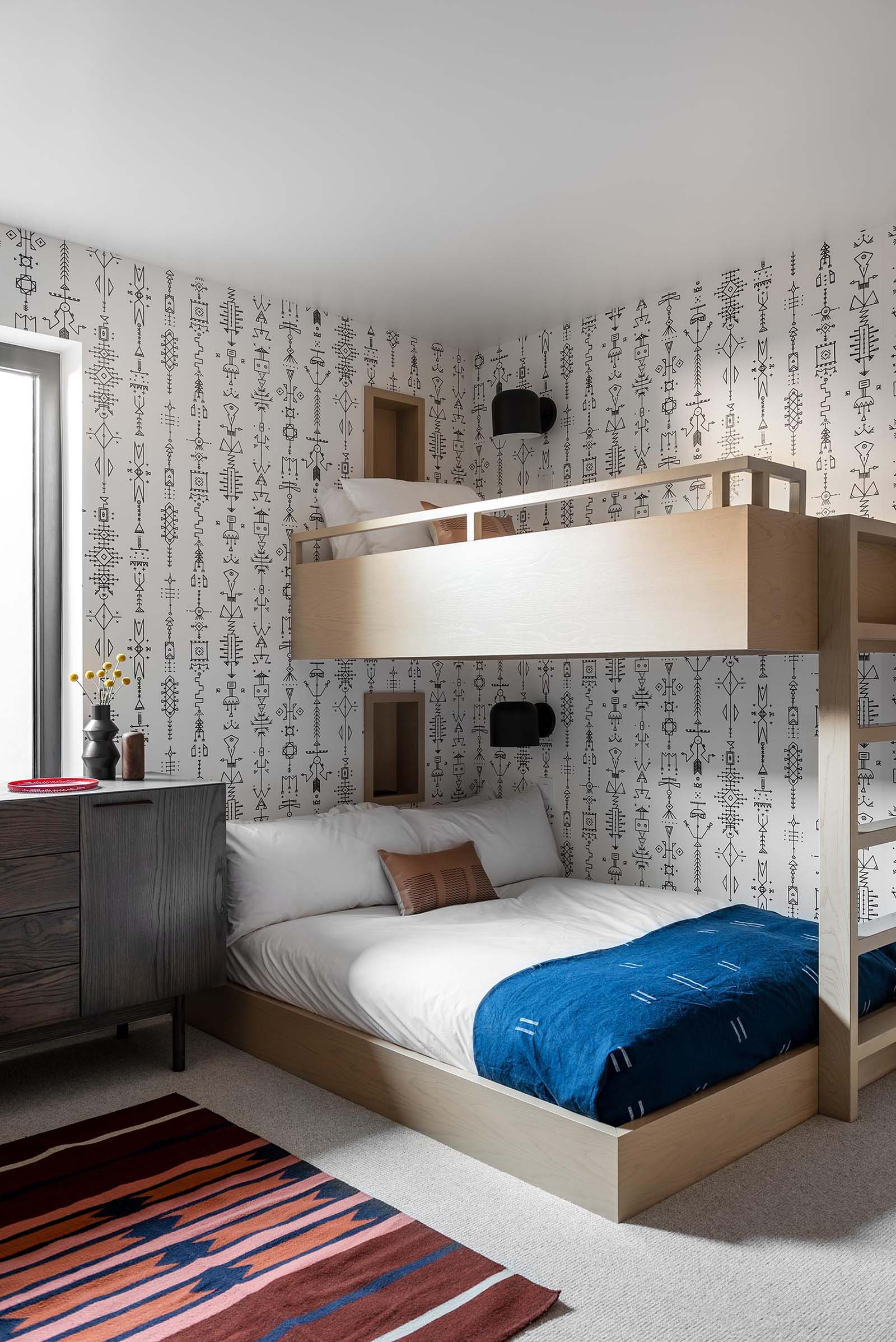 In this modern bedroom, a graphic wallpaper wraps around the room, while bunk beds are designed to sleep three people, and each bed has a small niche and wall mounted matte black light.