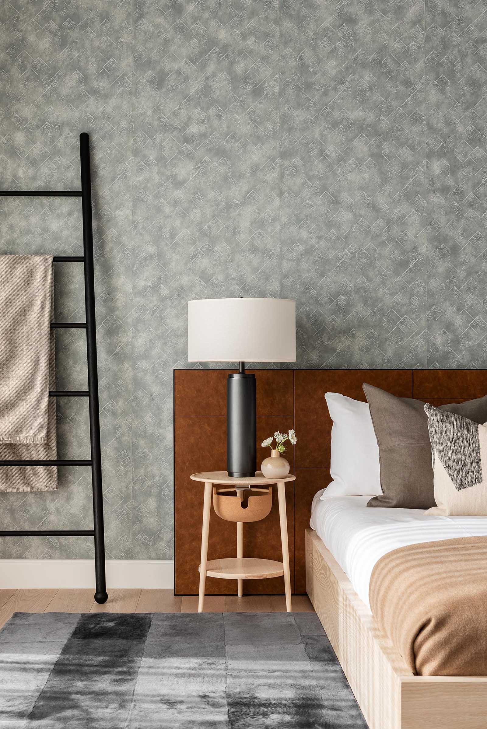In this modern bedroom, there's a muted gray wallpaper that covers the entire wall, creating a backdrop for the bed, while minimalist pendant light hangs from the ceiling, and a matte black ladder provides a place to hang blankets.