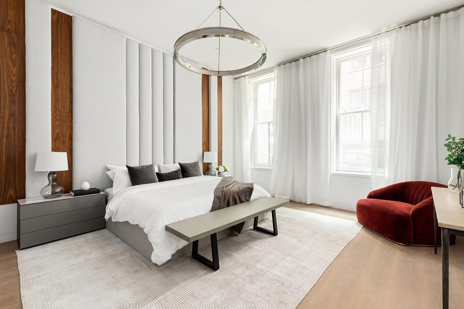 This modern master suite includes a custom wood and upholstered panel headboard that draws the eye upwards to the ceiling, making the room feel even larger than it is.