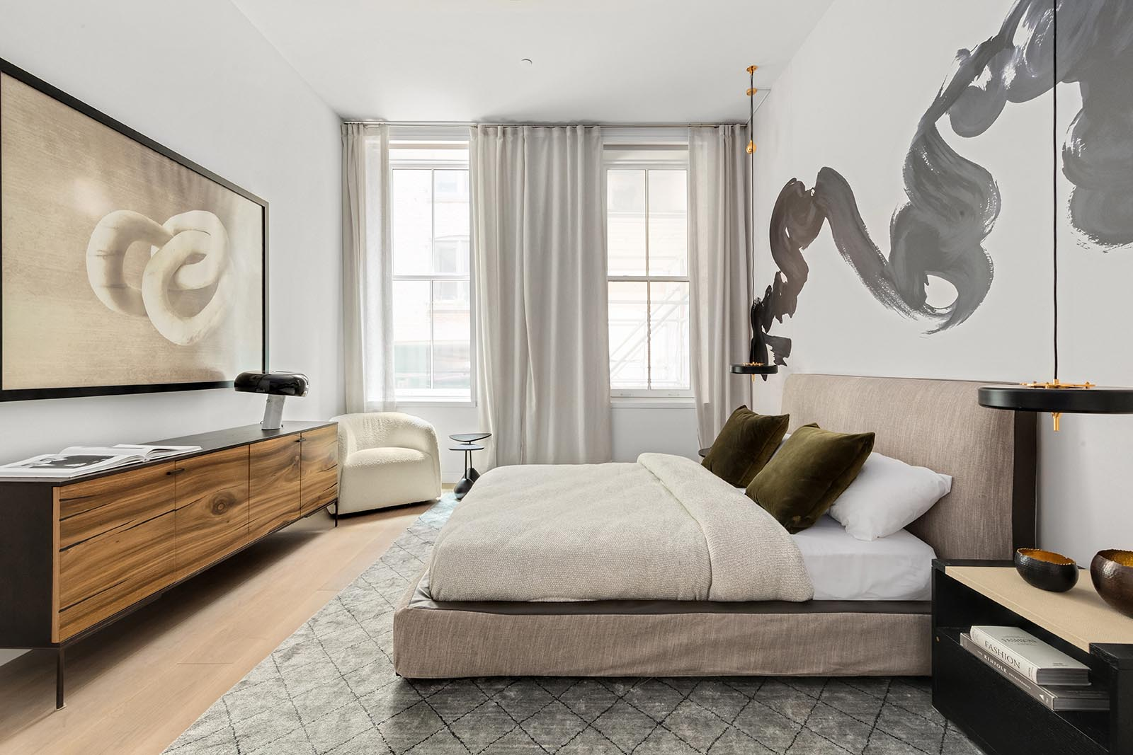 In this modern bedroom, large artwork has been used to fill the white walls.