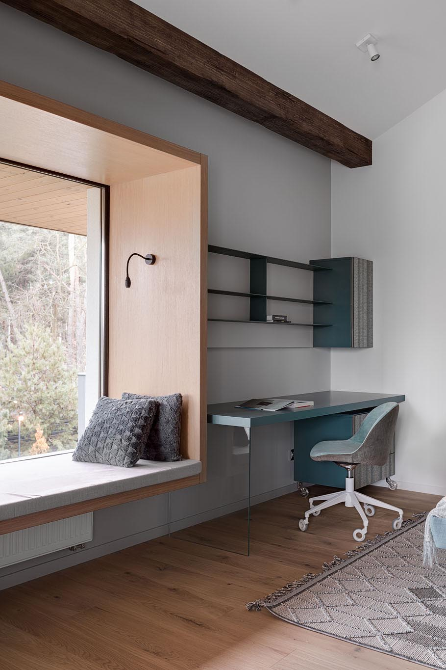 In this modern bedroom, there's a custom designed built-in window seat with views of the neighborhood. The bedroom also includes a desk with shelving above, and exposed wood beams.