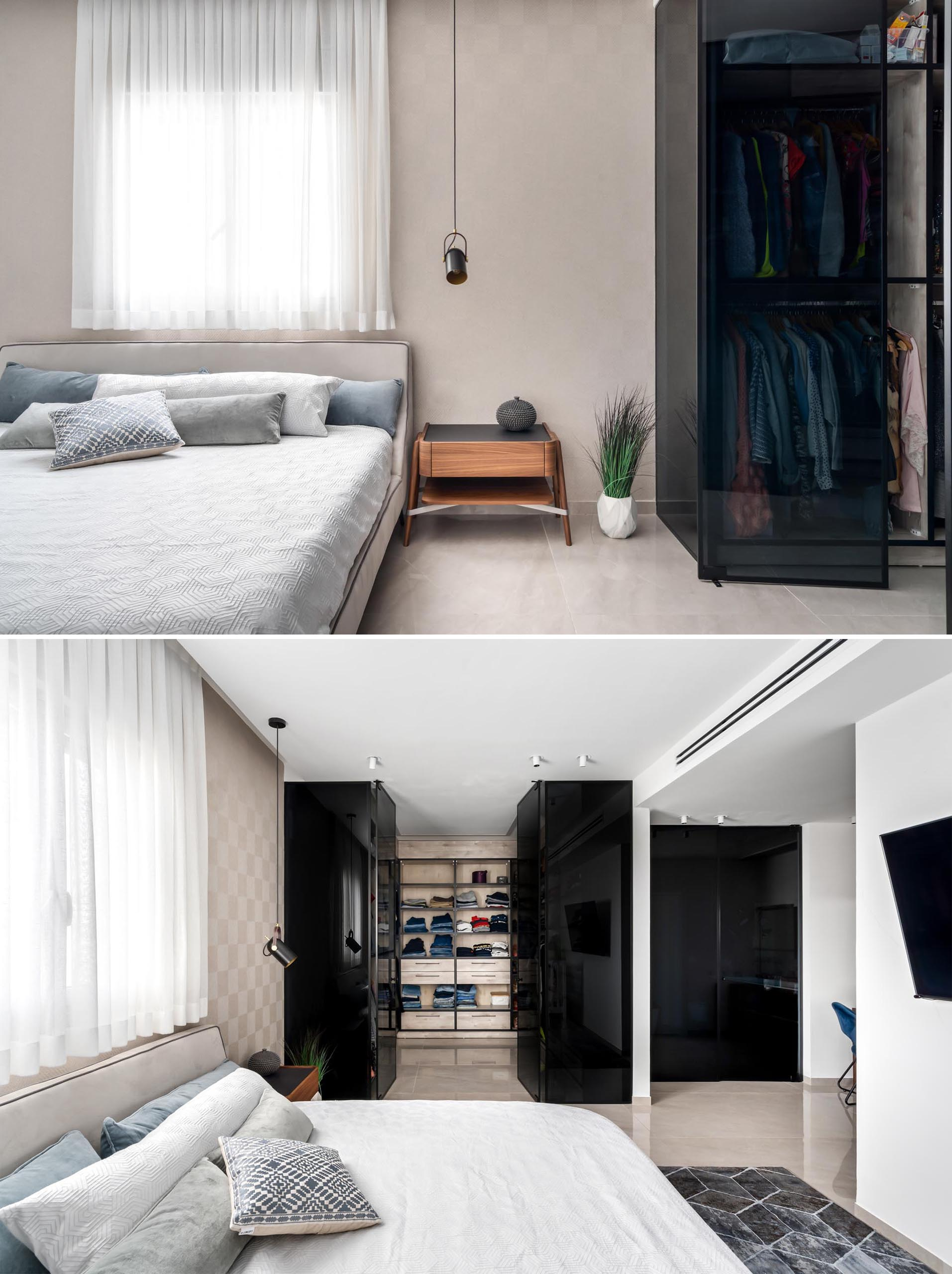 In this primary bedroom, light walls are contrasted by a black glass walk-in closet.