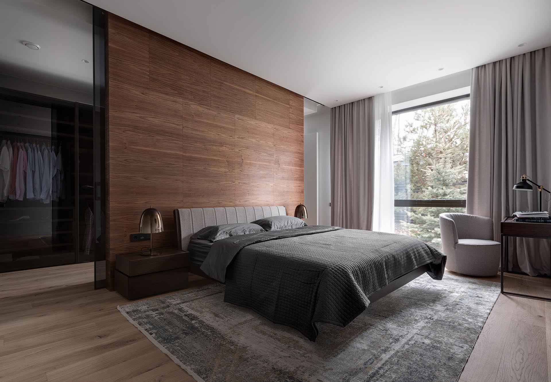 In this modern primary bedroom suite, there's a wood accent wall that separates the bedroom from the walk-through closet, that also includes black glass doors.